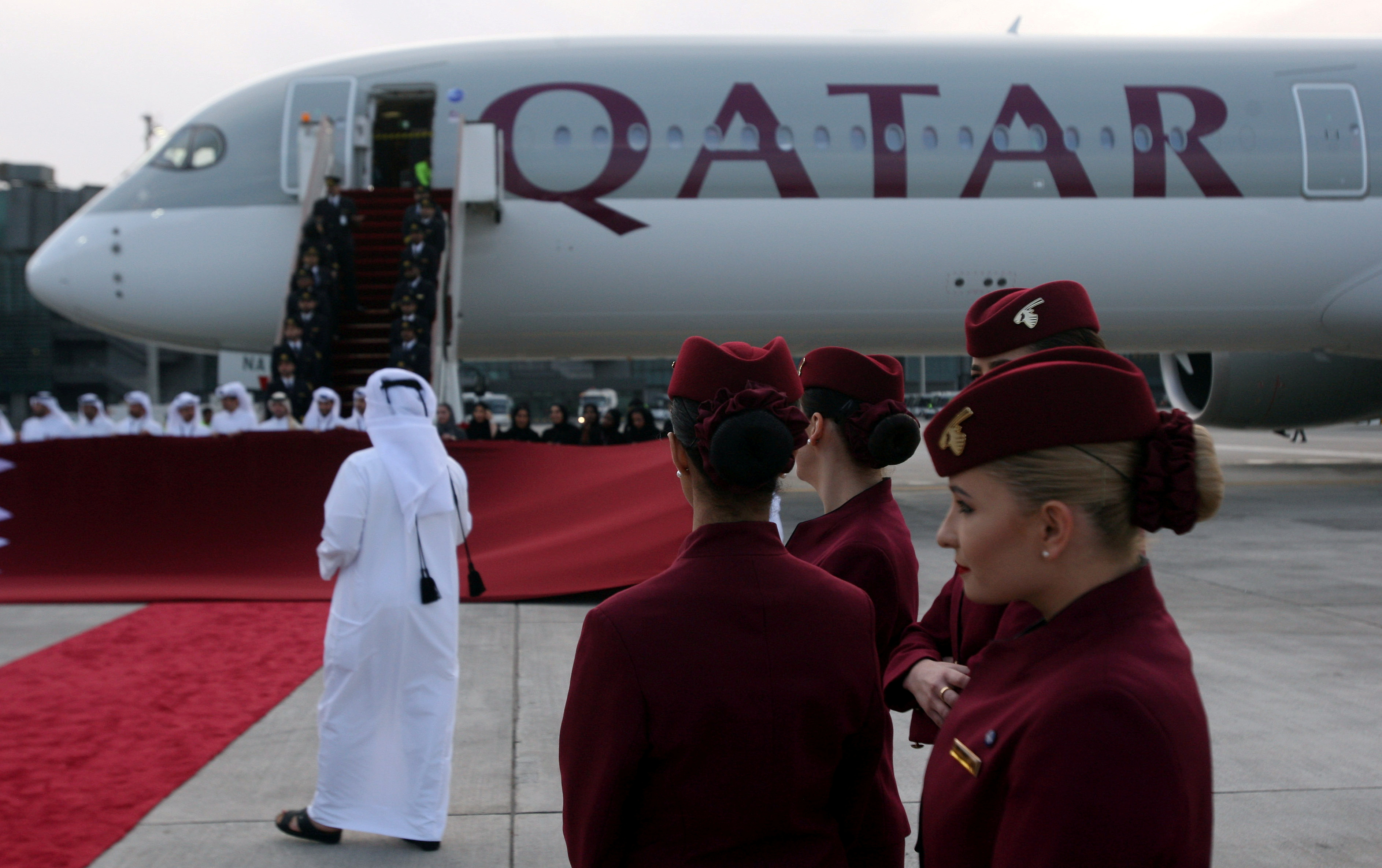 Qatar Airways cabin crew stand in front of an Airbus A350-1000 at Hamad International Airport in Doha, Qatar, February 21, 2018. REUTERS/Naseem Zeitoon/File Photo