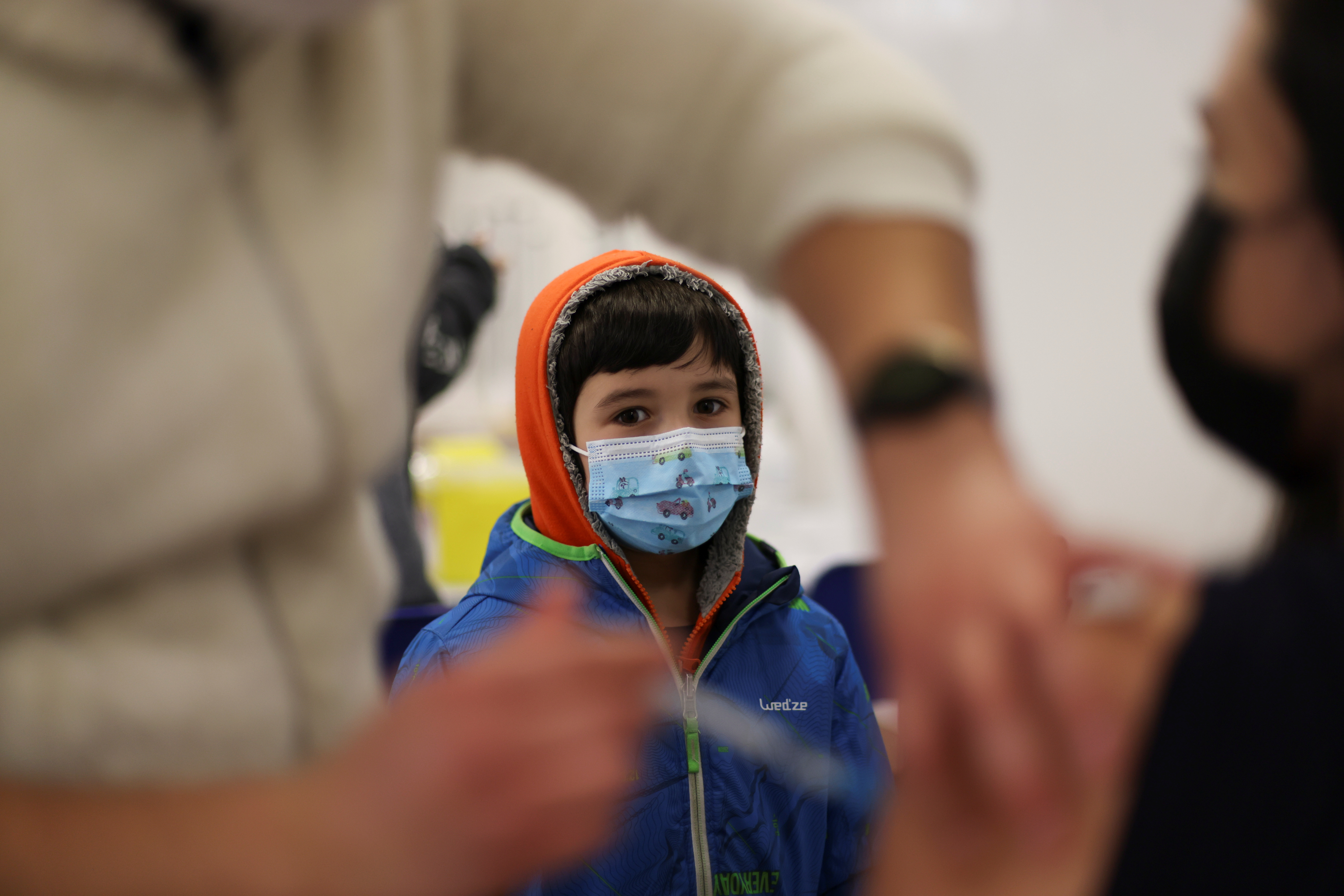 A child looks on as a woman receives a dose of Pfizer/BioNTech coronavirus disease (COVID-19) vaccine during a vaccination campaign inside the University of Santiago, Chile June 30, 2021. REUTERS/Ivan Alvarado/File Photo