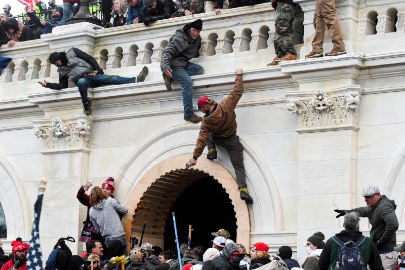 Supporters of U.S. President Donald Trump climb on walls at the U.S. Capitol during a protest against the certification of the 2020 U.S. presidential election results by the U.S. Congress, in Washington, U.S., January 6, 2021. REUTERS/Stephanie Keith/File Photo