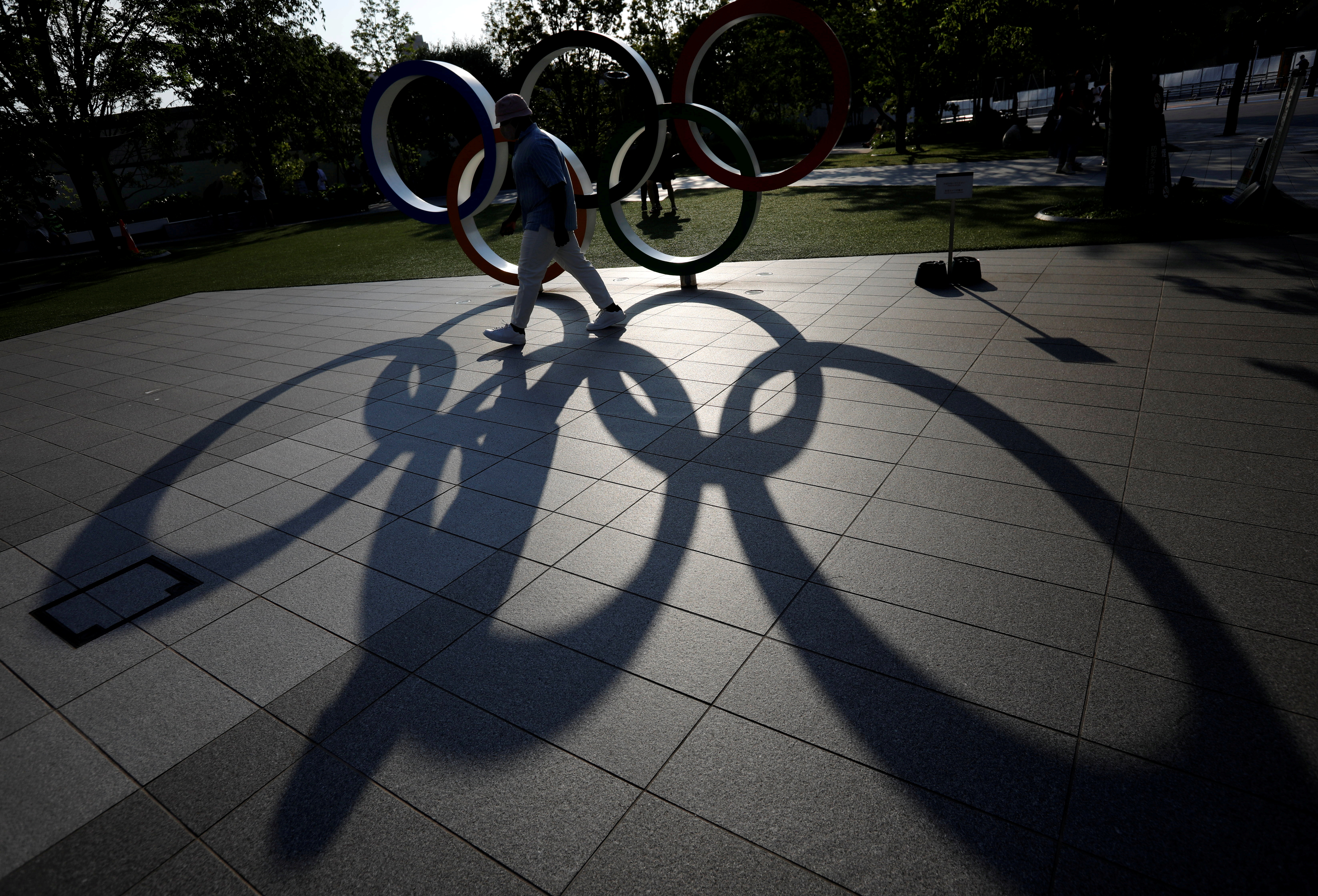 A visitor and the Olympic Rings monument cast shadows on the ground outside the Japan Olympic Committee (JOC) headquarters near the National Stadium, the main stadium for the 2020 Tokyo Olympic Games that have been postponed to 2021 due to the coronavirus disease (COVID-19) outbreak, in Tokyo, Japan May 30, 2021.  REUTERS/Issei Kato/File Photo