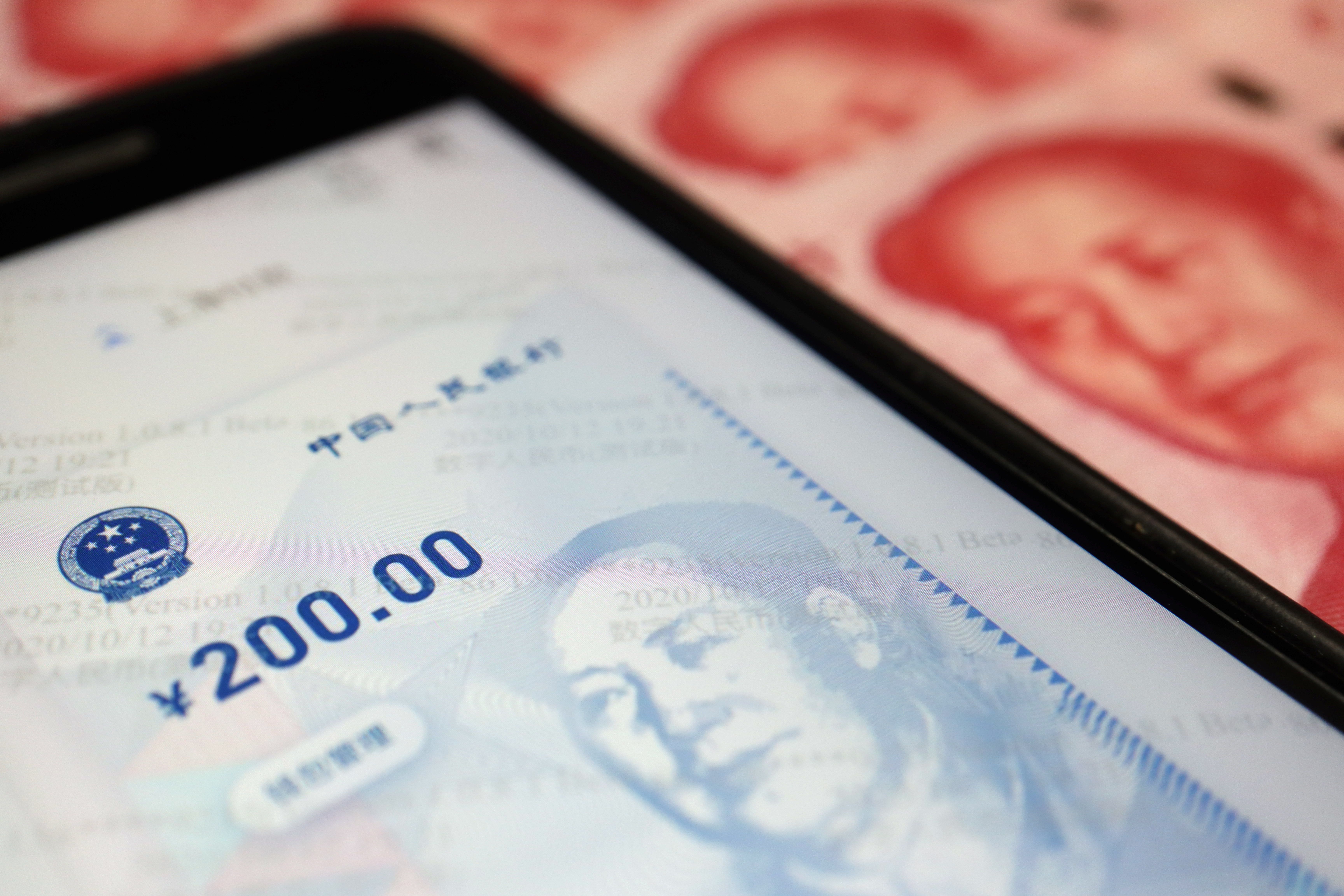 China's official app for digital yuan is seen on a mobile phone next to 100-yuan banknotes in this illustration picture taken October 16, 2020.