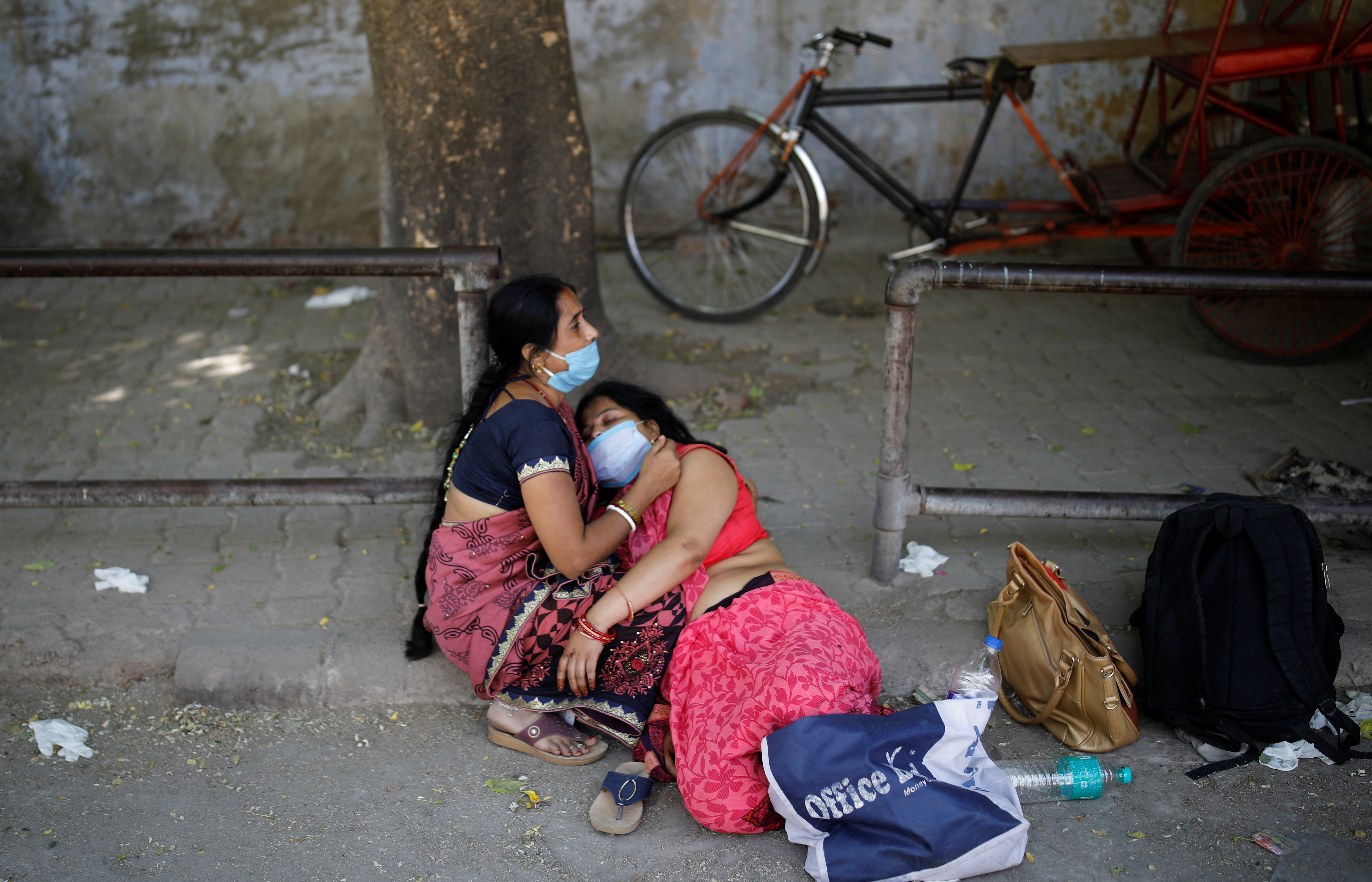 Women mourn the death of a family member, who died from the coronavirus disease (COVID-19), outside a crematorium in New Delhi, India April 24, 2021. REUTERS/Adnan Abidi