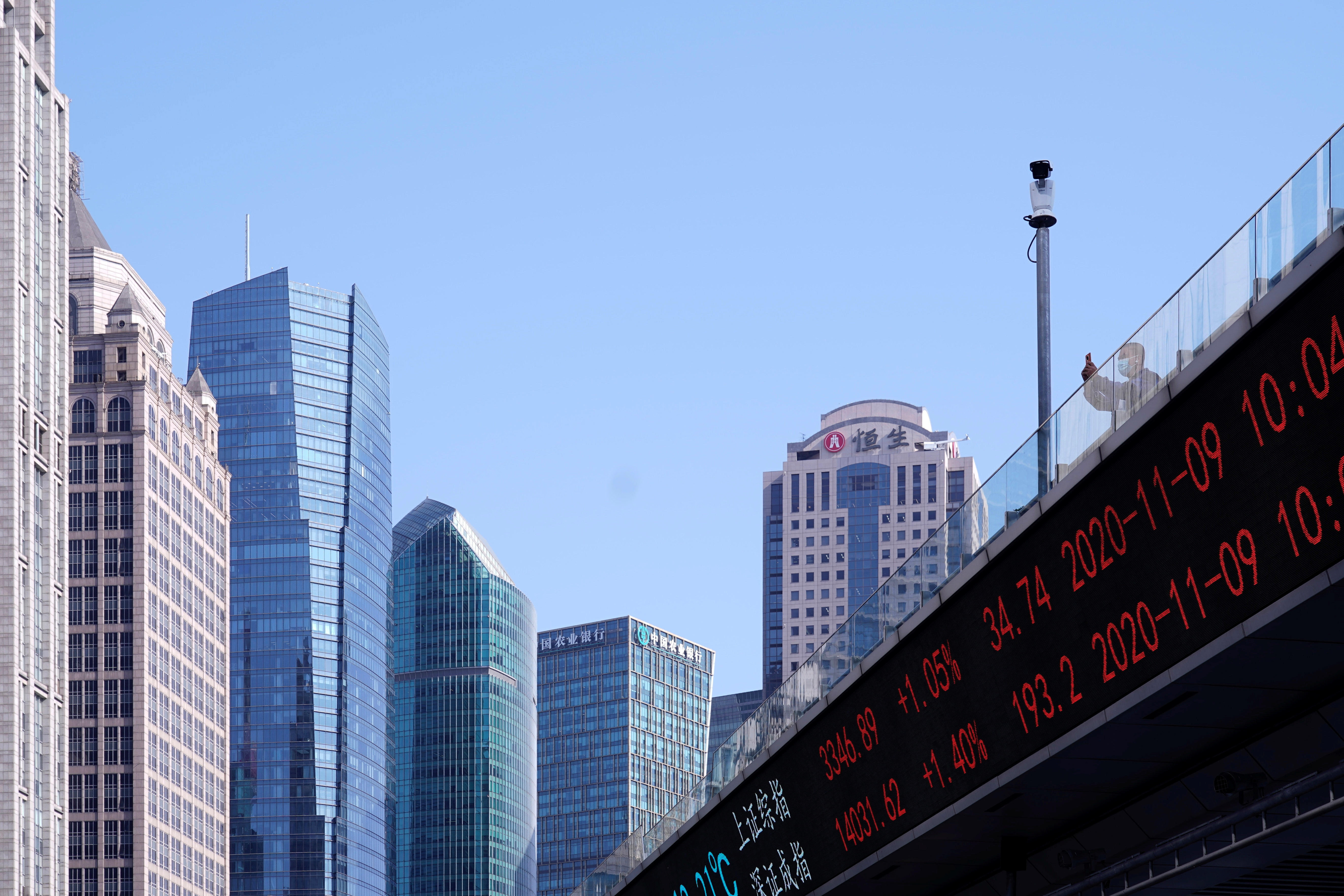 An electronic board showing Shanghai and Shenzhen stock indexes is seen on an overpass at the Lujiazui financial district in Shanghai, China November 9, 2020. REUTERS/Aly Song/File photo
