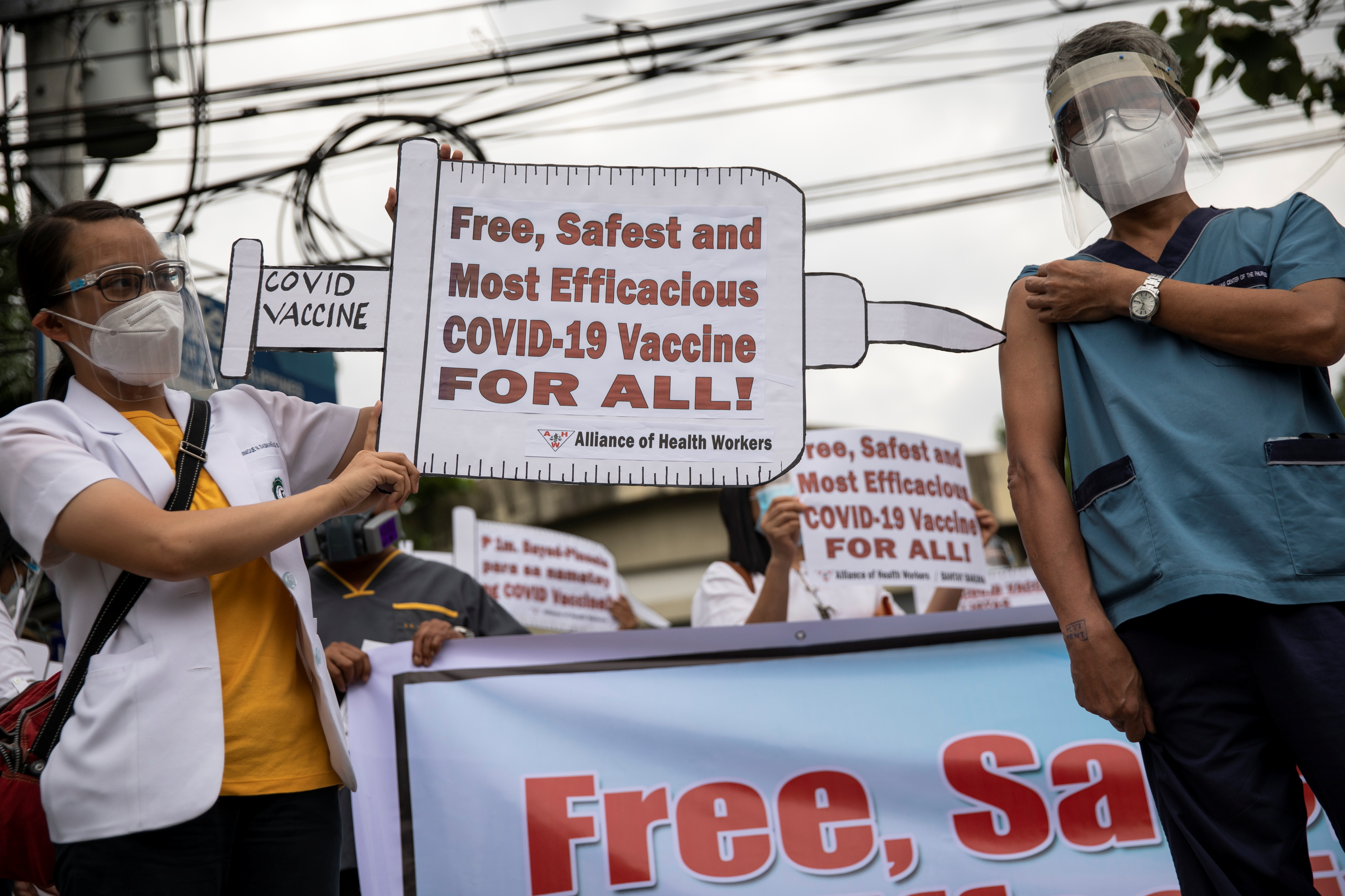 Health workers stage a protest calling for free, safe, and most efficacious coronavirus disease (COVID-19) vaccines, as the government kicks off its COVID-19 vaccination campaign with Sinovac Biotech's CoronaVac vaccines, outside the Lung Center of the Philippines, Quezon City, Metro Manila, Philippines, March 1, 2021. REUTERS/Eloisa Lopez