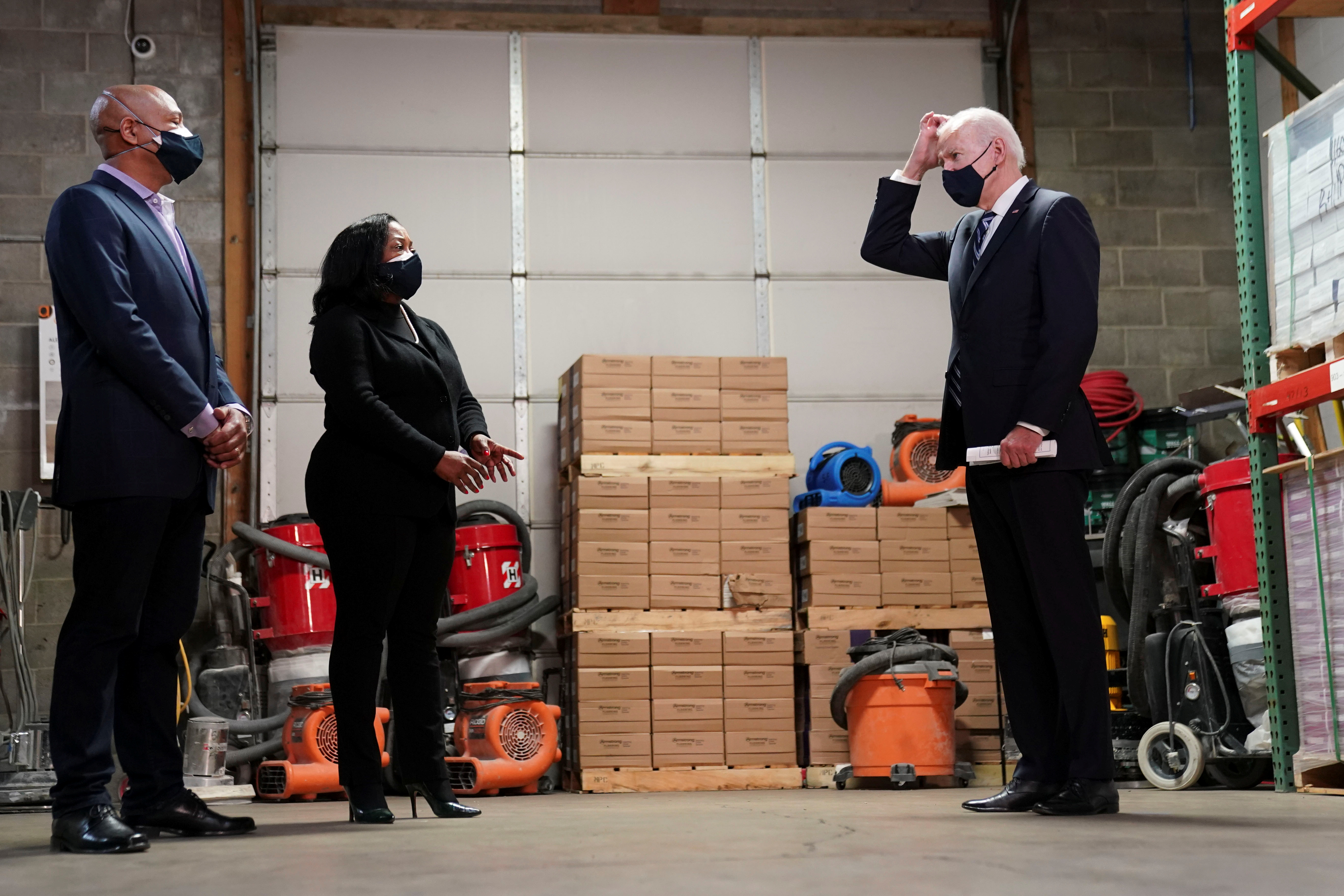 U.S. President Joe Biden speaks with owners James Smith and Kristin Smith during a