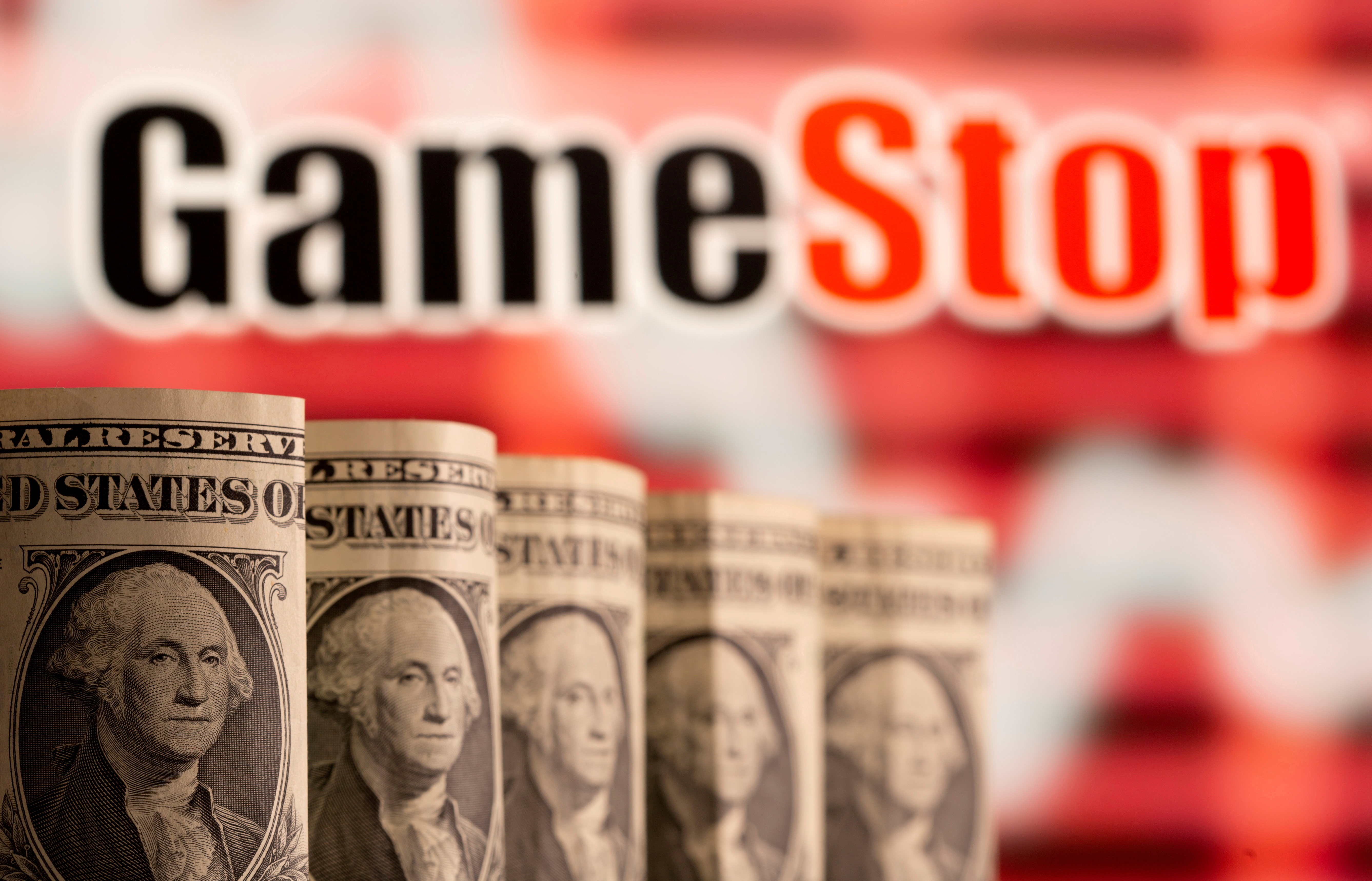 U.S. one dollar banknotes are seen in front of displayed GameStop logo in this illustration taken February 8, 2021. REUTERS/Dado Ruvic/Illustration/File Photo
