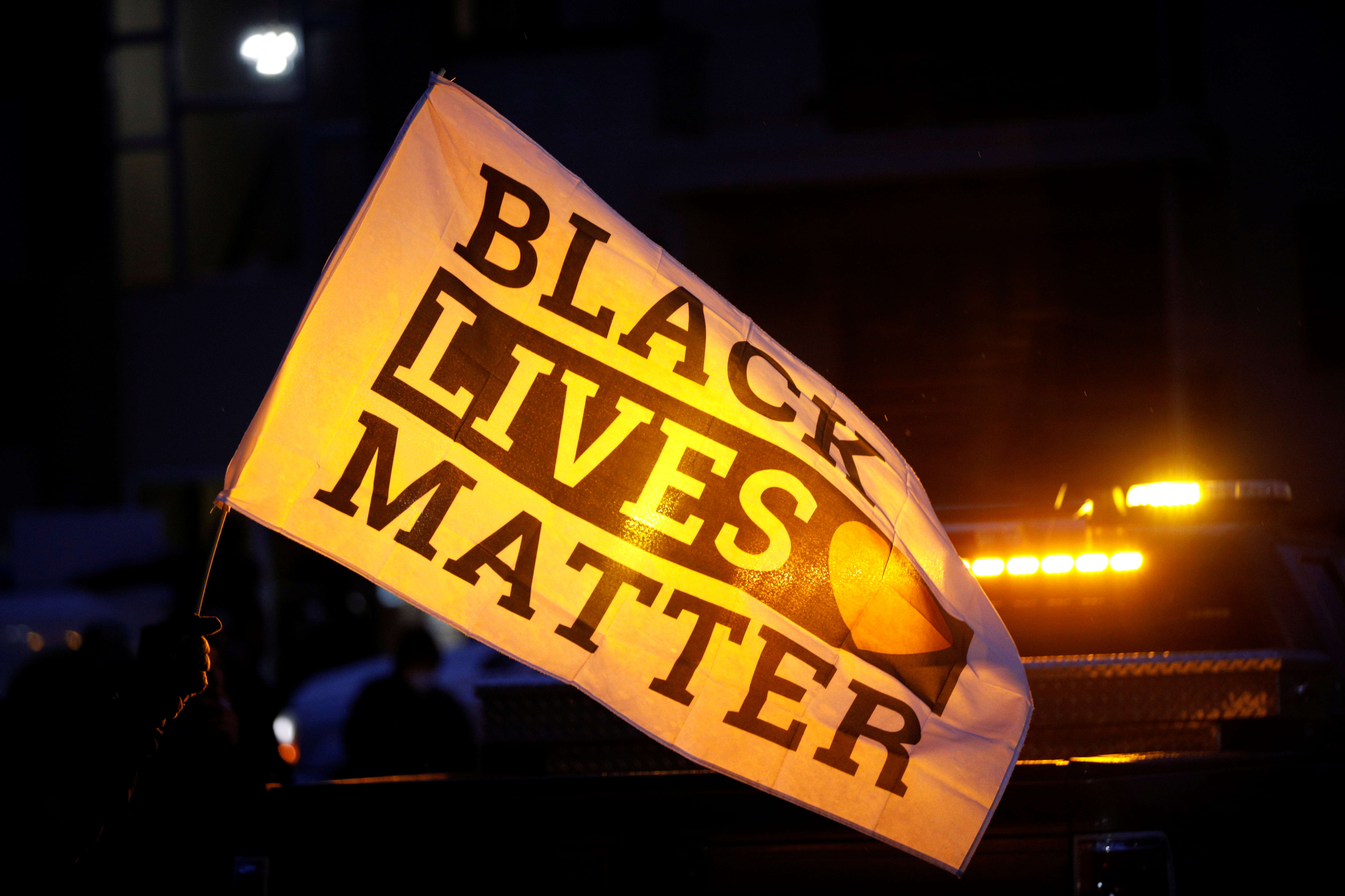 A protester holds a Black Lives Matter flag outside the Brooklyn Center Police Department, as protests continue days after former police officer Kim Potter fatally shot Daunte Wright, in Brooklyn Center, Minnesota, U.S. April 14, 2021. REUTERS/Nick Pfosi