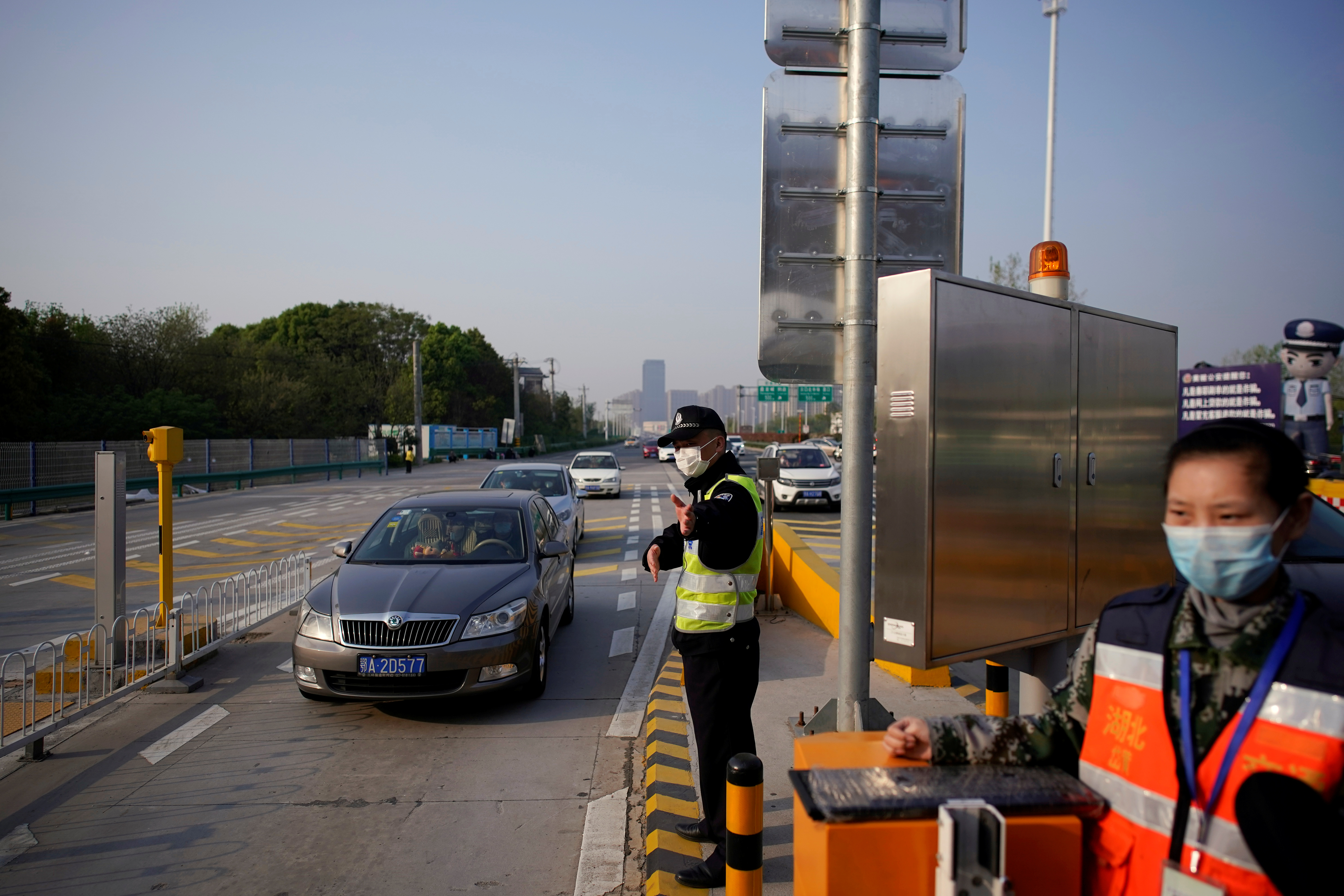 A police officer directs vehicles at a toll station of an expressway after travel restrictions to leave Wuhan, the capital of Hubei province and China's epicentre of the novel coronavirus disease (COVID-19) outbreak, were lifted, April 8, 2020. REUTERS/Aly Song