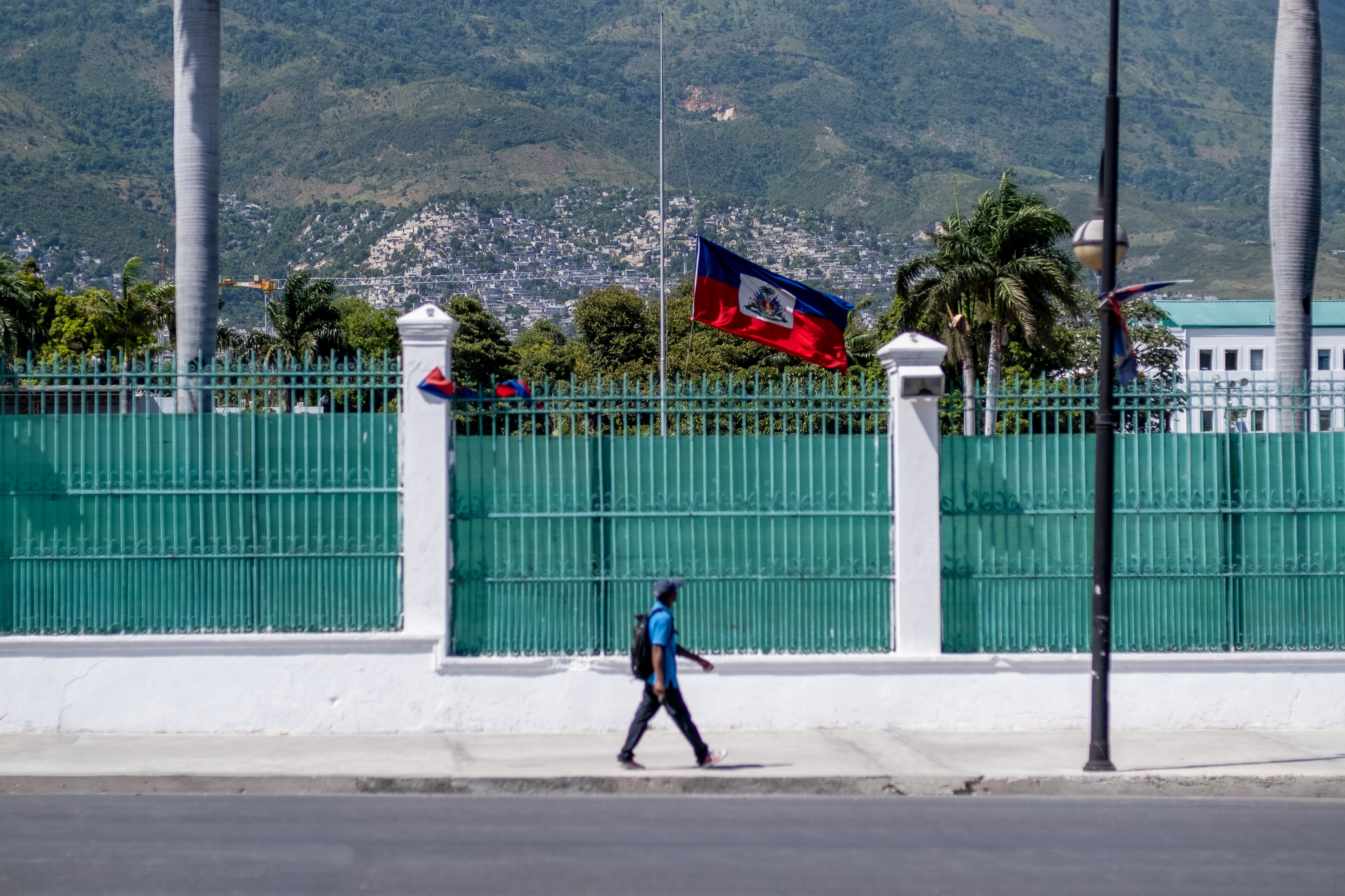 A man walks past in front of where the Haitian Presidential Palace used to be with the Haitian national flag at half-mast, following the assassination of President Jovenel Moise, in Port-au-Prince, Haiti July 10, 2021.  REUTERS/Ricardo Arduengo