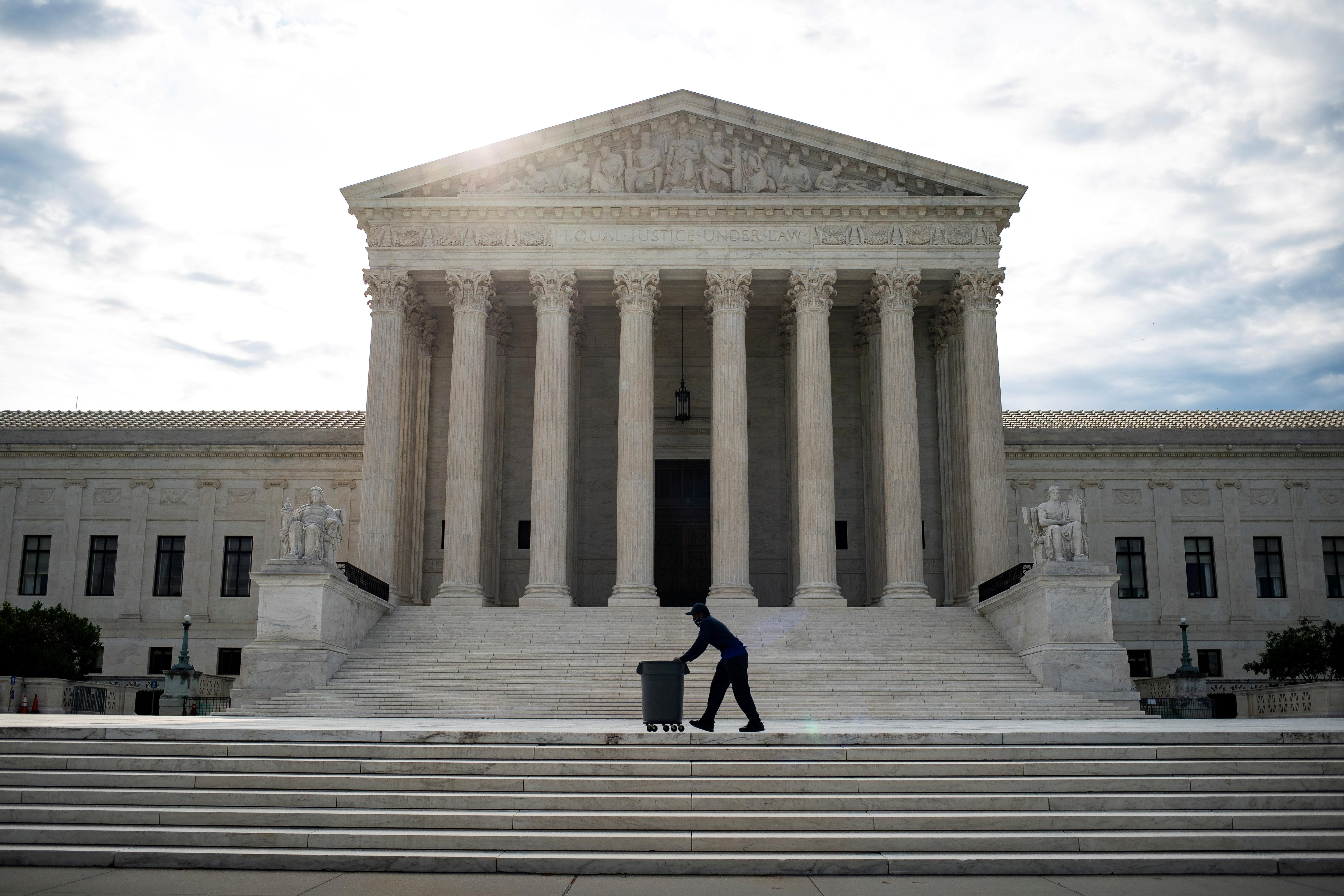 A man wheels a trash bins past the U.S. Supreme Court building in Washington, U.S., June 25, 2020. REUTERS/Al Drago/