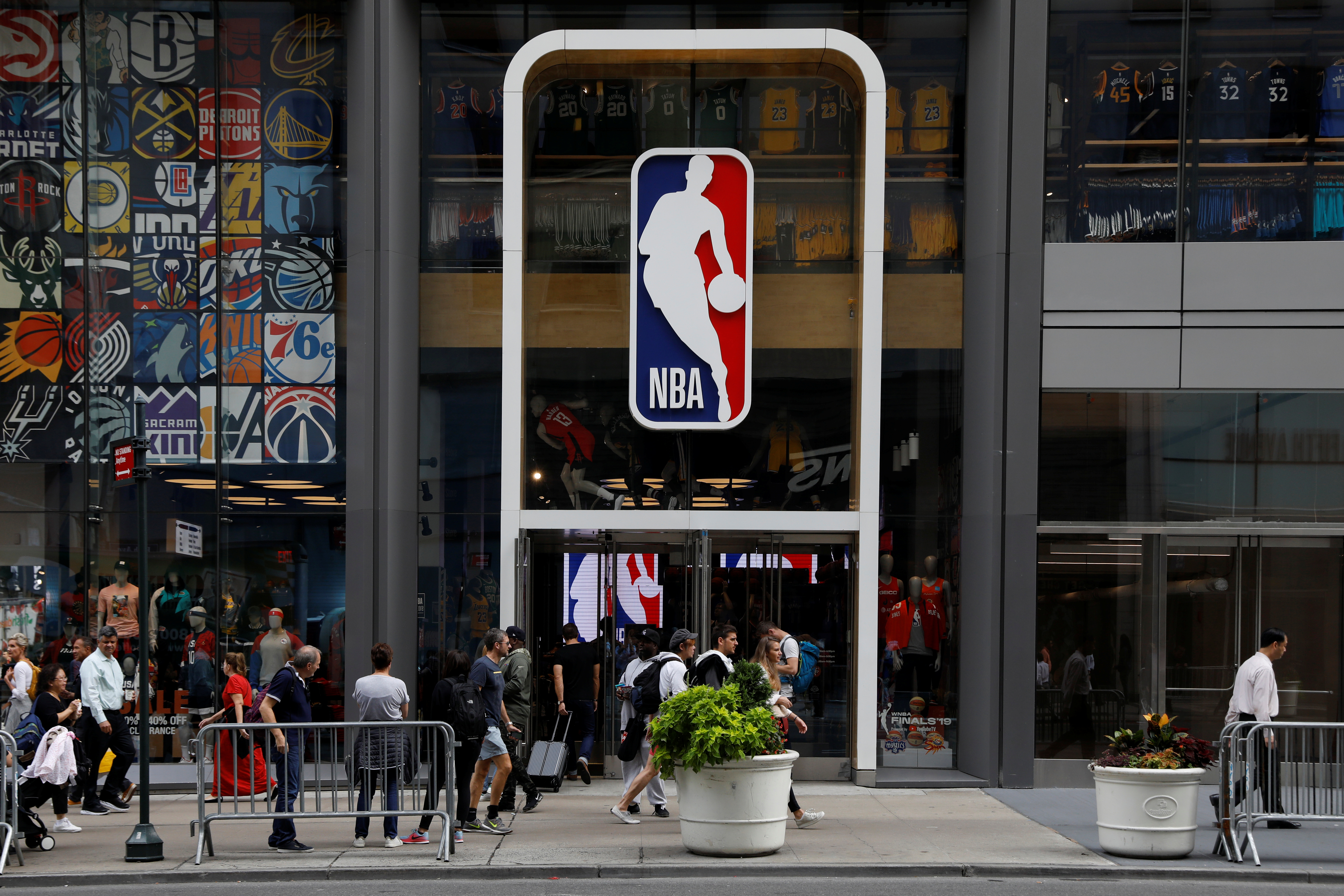 The NBA logo is displayed as people pass by the NBA Store in New York City, U.S., October 7, 2019. REUTERS/Brendan McDermid
