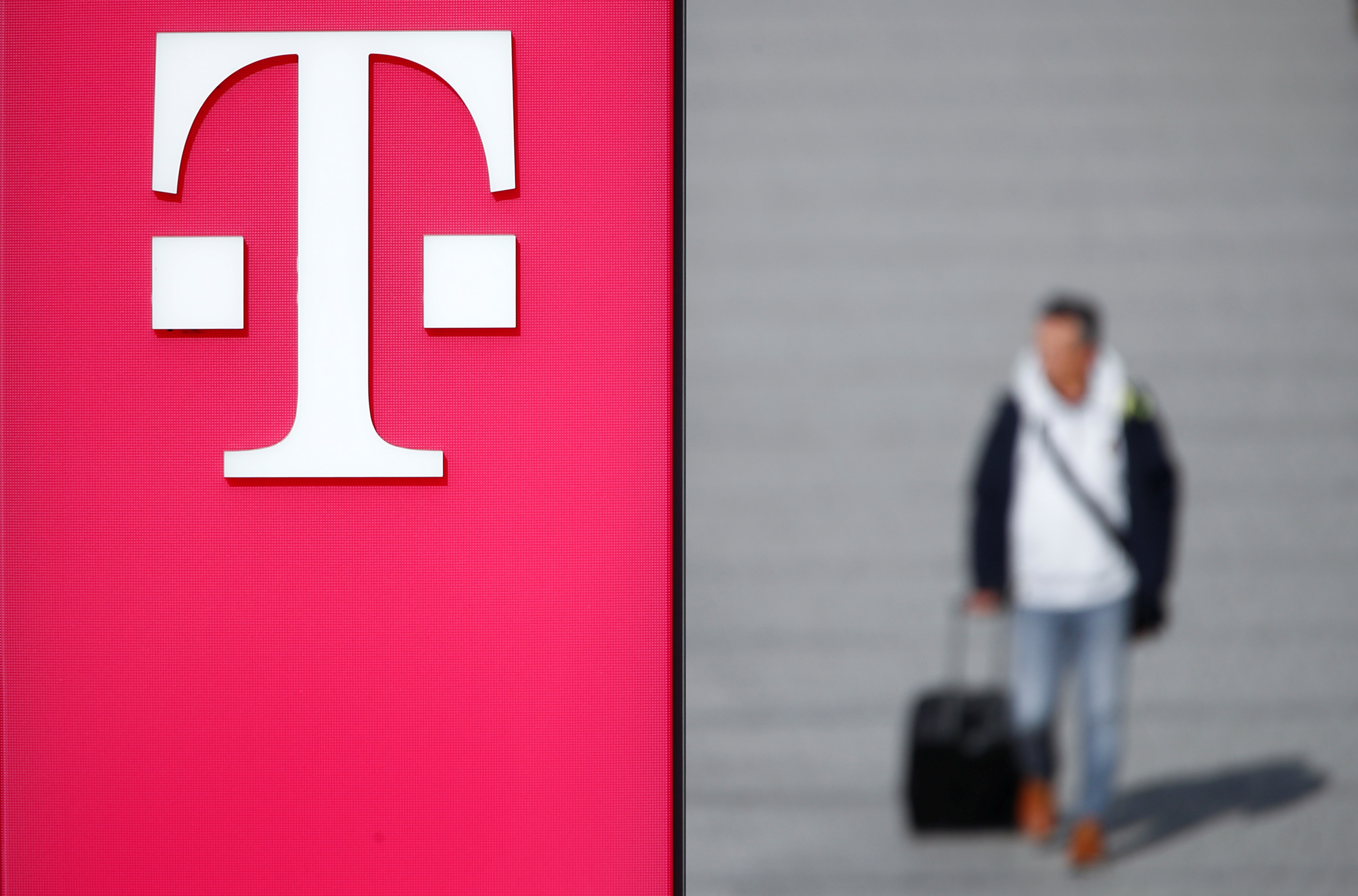A man walks past the logo of Deutsche Telekom AG at the headquarters of German telecommunications giant in Bonn, Germany, February 19, 2019.   REUTERS/Wolfgang Rattay