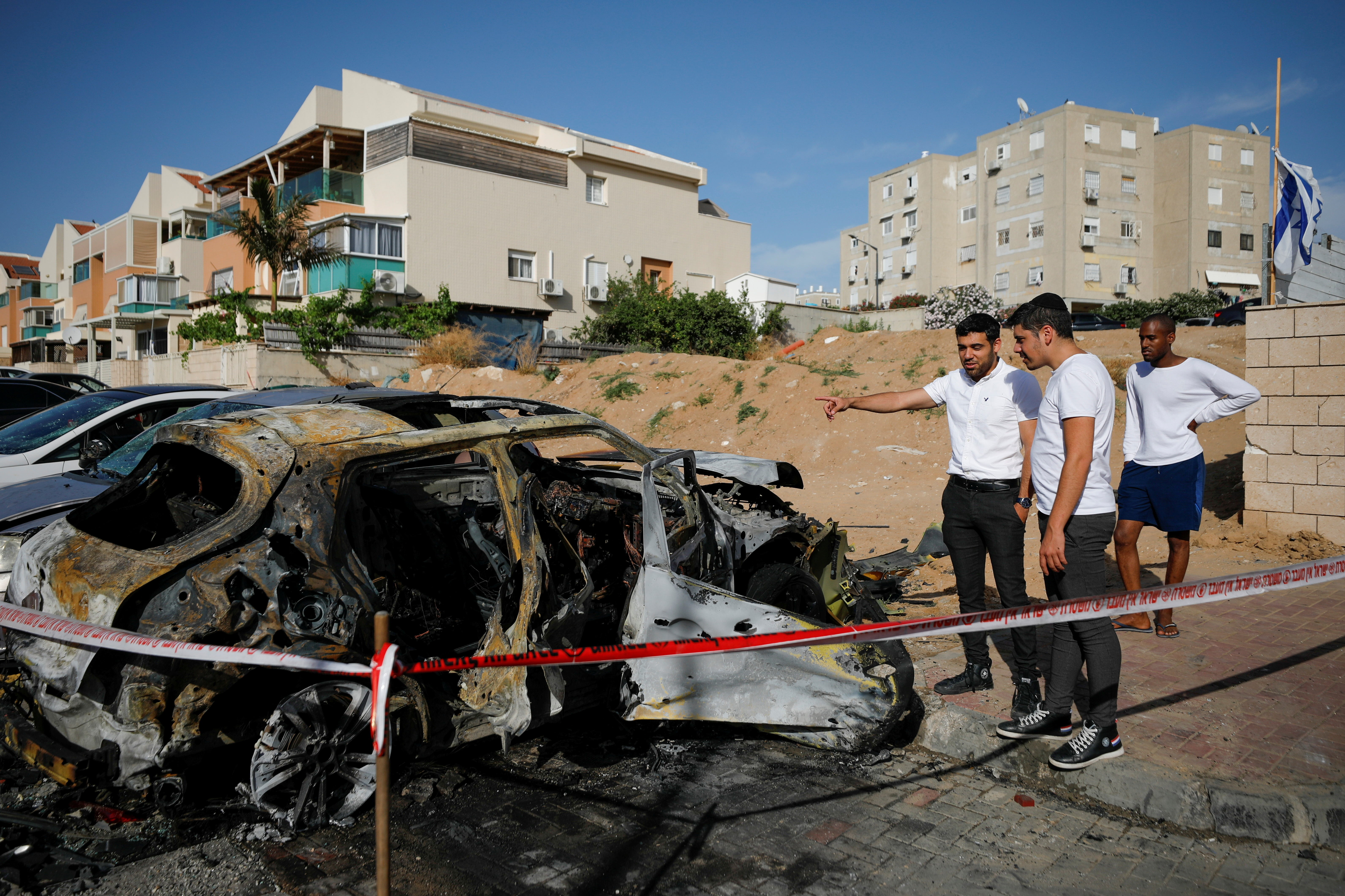 People look at a damaged car at a site where a rocket fired from Gaza landed, as Israeli-Palestinian cross-border violence continues, in Ashkelon, southern Israel, May 16, 2021. REUTERS/Amir Cohen