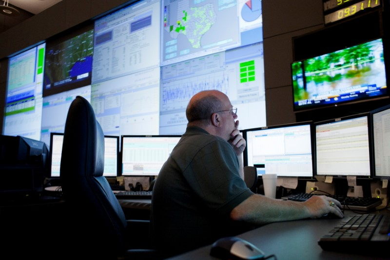 Reliability Coordinator Steven Andrews monitors power use on the big screen during a tour of the Electric Reliability Council of Texas (ERCOT) command center in Taylor, Texas August 14, 2012. REUTERS/Julia Robinson/File Photo