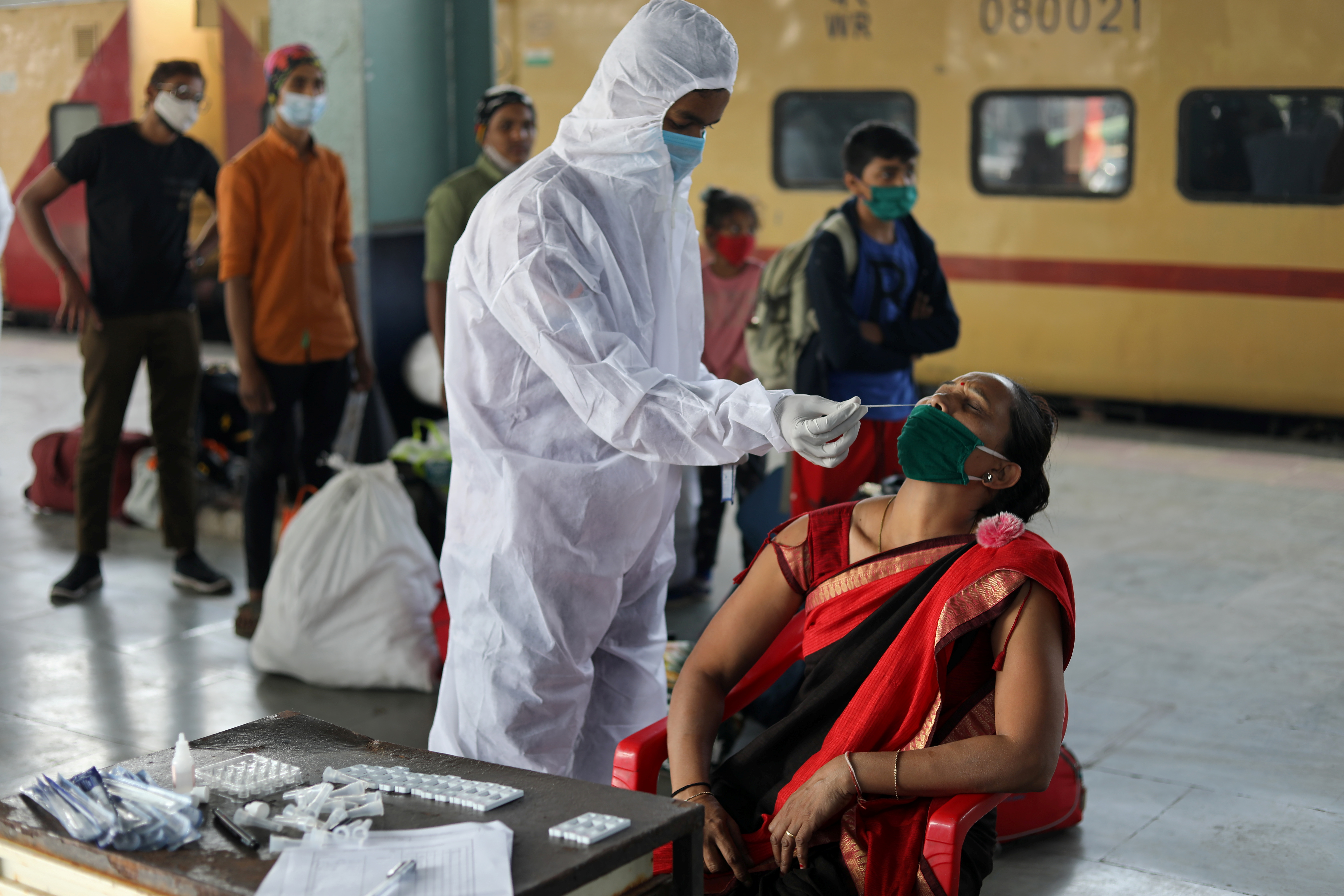 A health worker in personal protective equipment (PPE) collects a swab sample from a woman during a rapid antigen testing campaign for the coronavirus disease (COVID-19), at a railway station platform in Mumbai, India, December 19, 2020. REUTERS/Francis Mascarenhas
