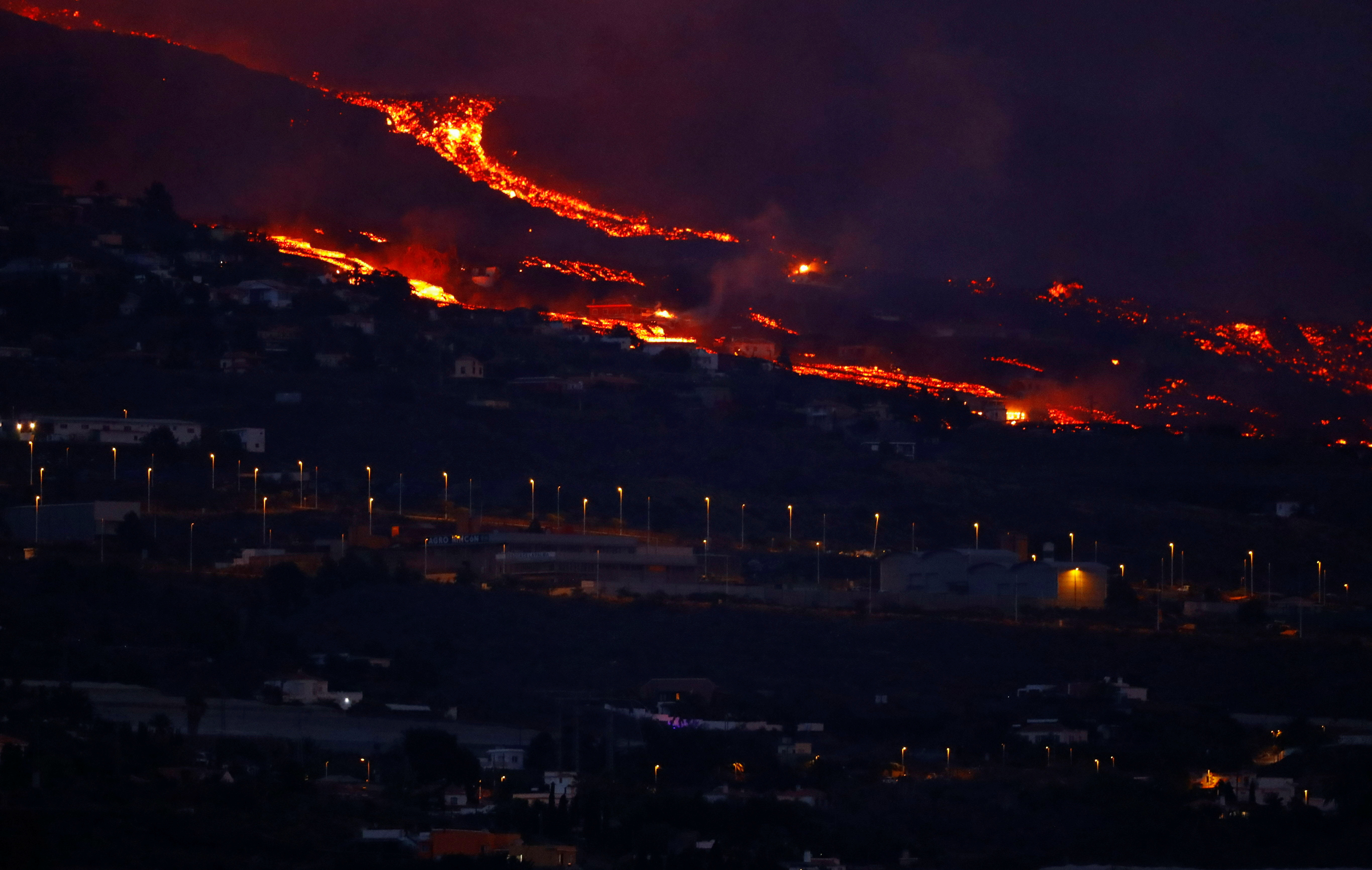 Lava flows behind houses following the eruption of a volcano in the Cumbre Vieja national park, in this picture taken from Tazacorte, on the Canary Island of La Palma, September 20, 2021. REUTERS/Borja Suarez