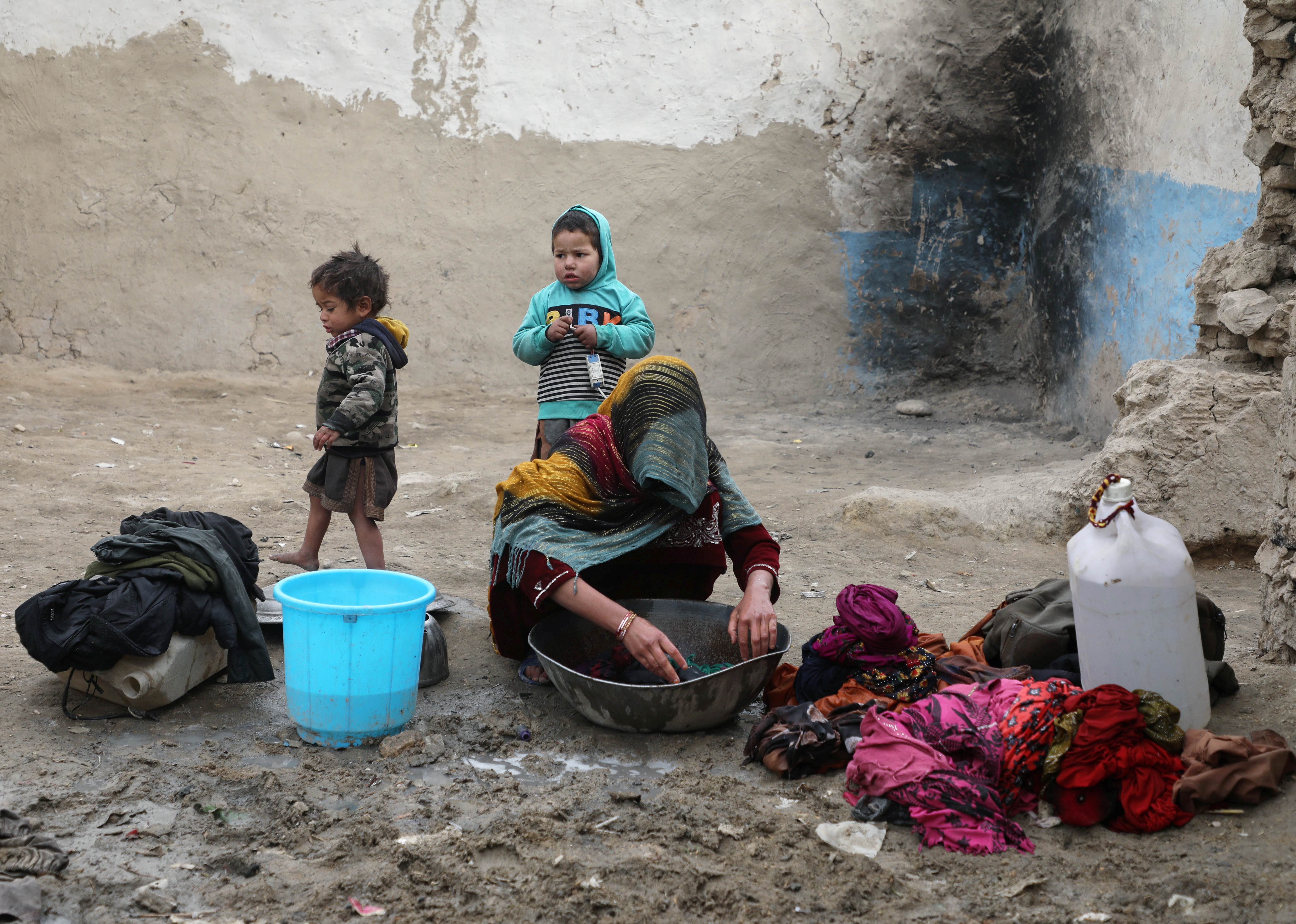 An internally displaced Afghan woman washes clothes outside her shelter on the outskirts of Kabul, Afghanistan February 3, 2021. REUTERS/Omar Sobhani