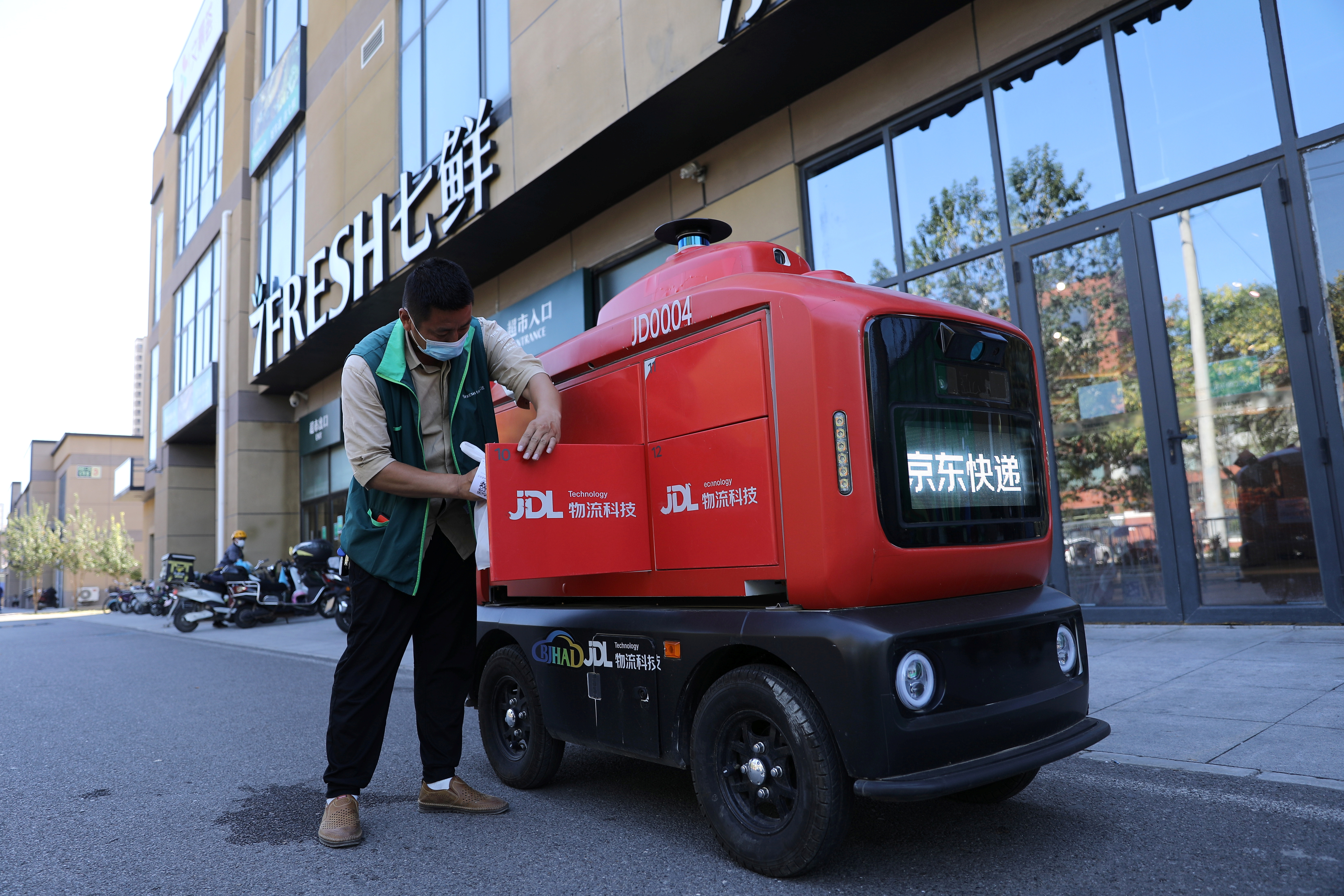 An employee from 7Fresh supermarket loads goods on an autonomous delivery vehicle by JD Logistics, the delivery arm of JD.com, in Beijing, China September 22, 2021. REUTERS/Tingshu Wang