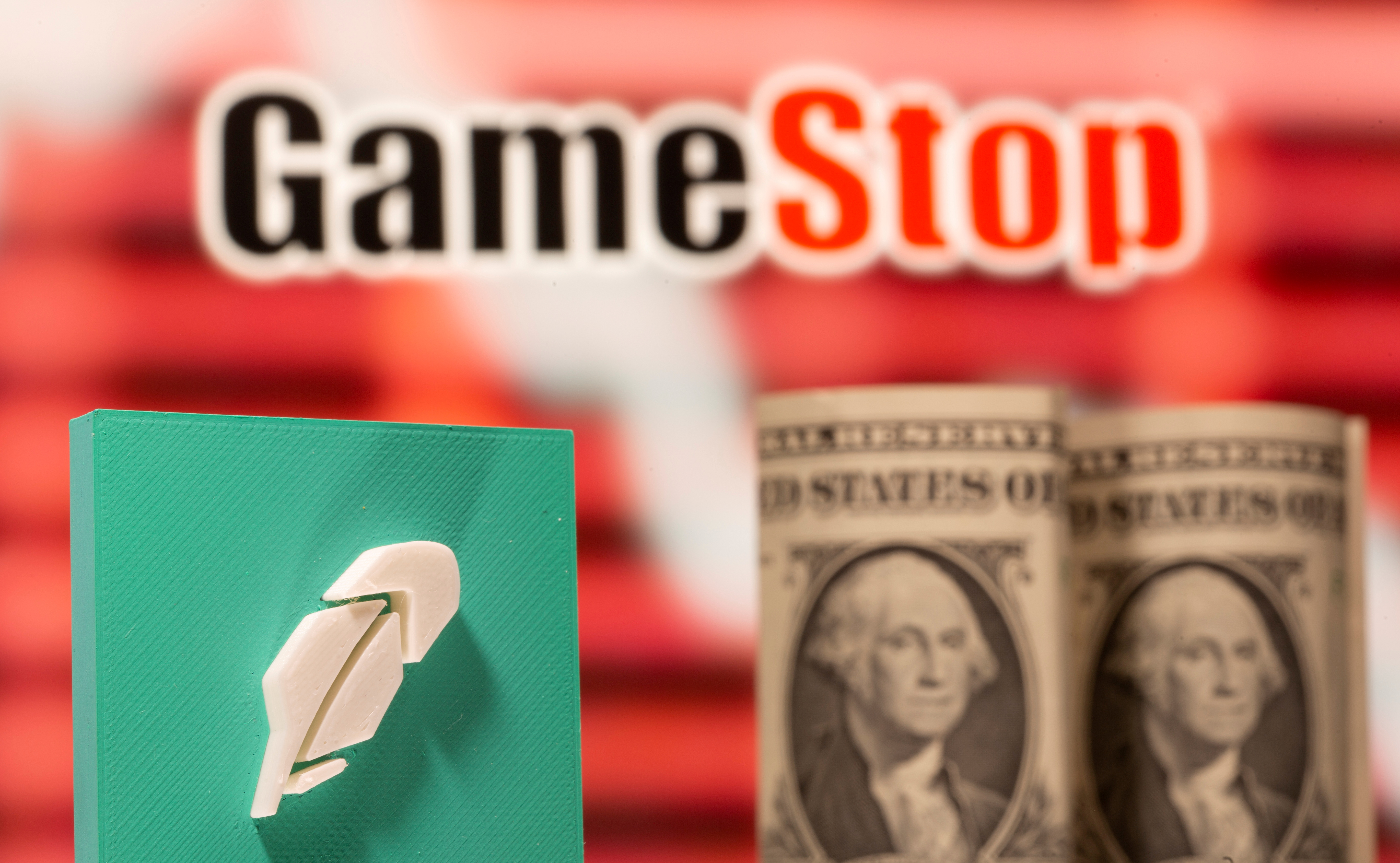 A 3d printed Robinhood logo and one dollar banknotes are seen in front of displayed GameStop logo in this illustration taken February 8, 2021. REUTERS/Dado Ruvic/Illustration