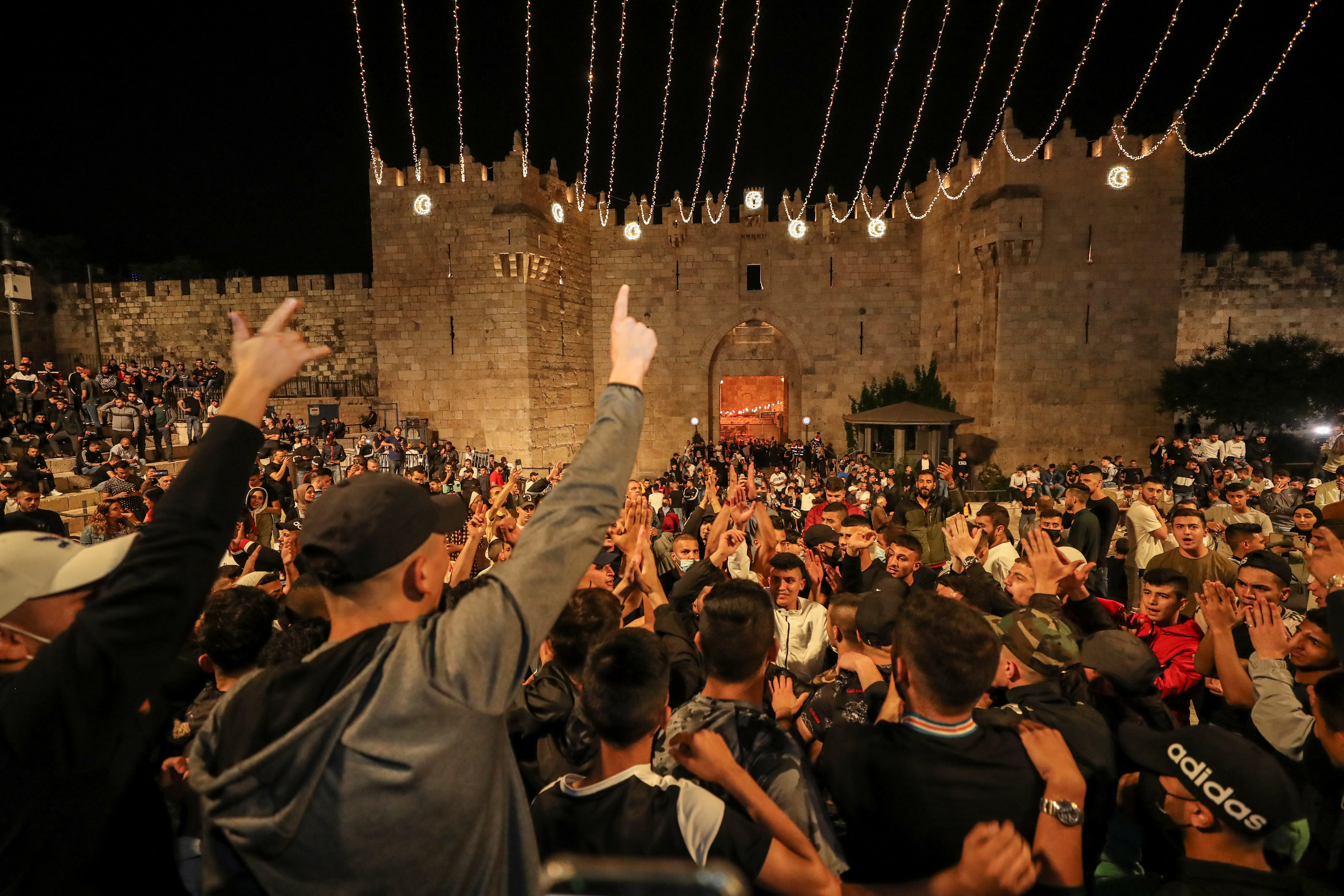 Palestinians celebrate outside Damascus Gate after the barriers that were put up by Israeli police are removed, allowing them to access the main square that has been the focus of a week of clashes around Jerusalem's Old City April 25, 2021. REUTERS/Ammar Awad