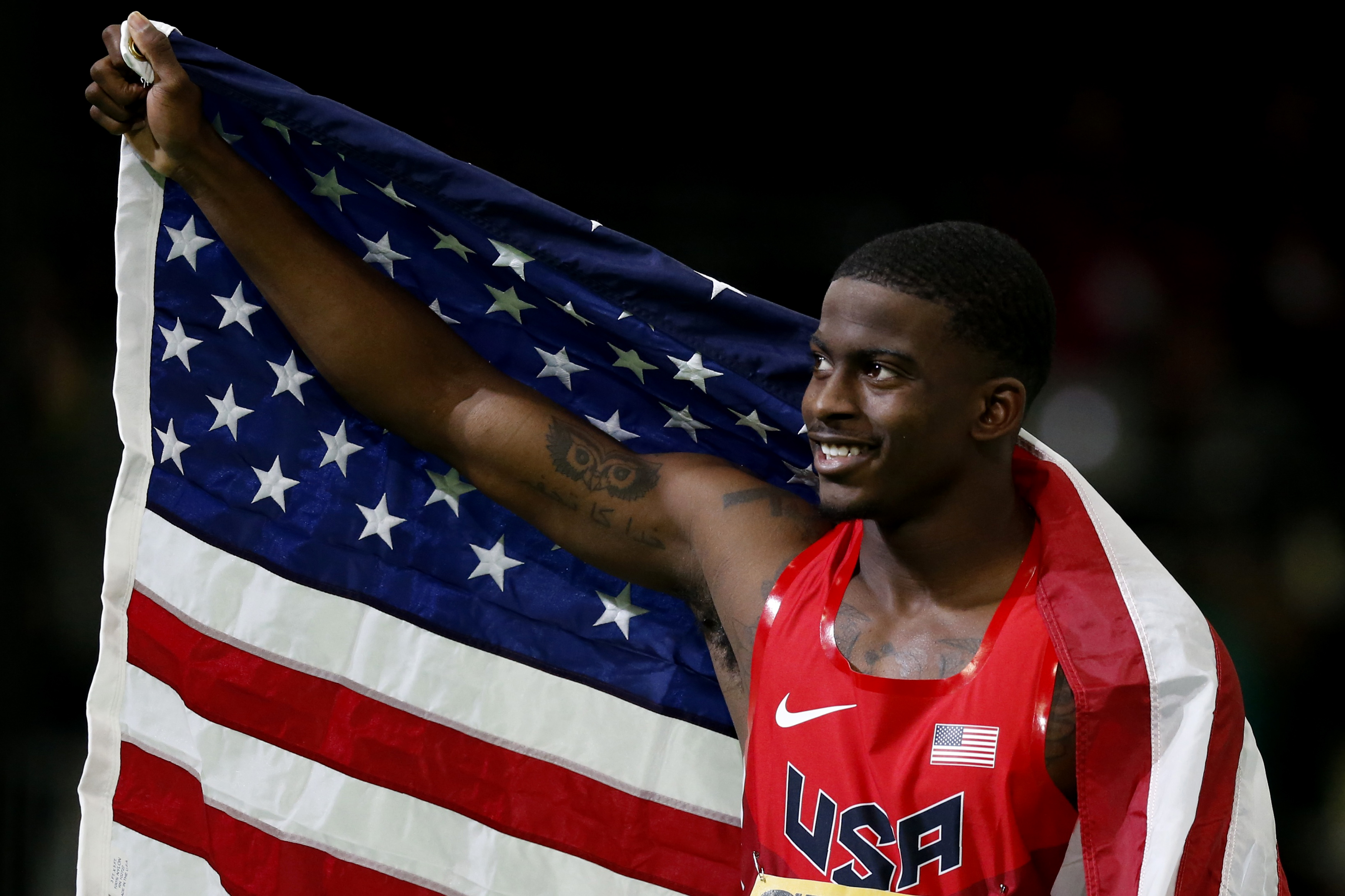 Trayvon Bromell of the U.S. celebrates with an American flag after winning the gold medal in the men's 60 meters at the IAAF World Indoor Athletics Championships in Portland, Oregon March 18, 2016.   REUTERS/Lucy Nicholson