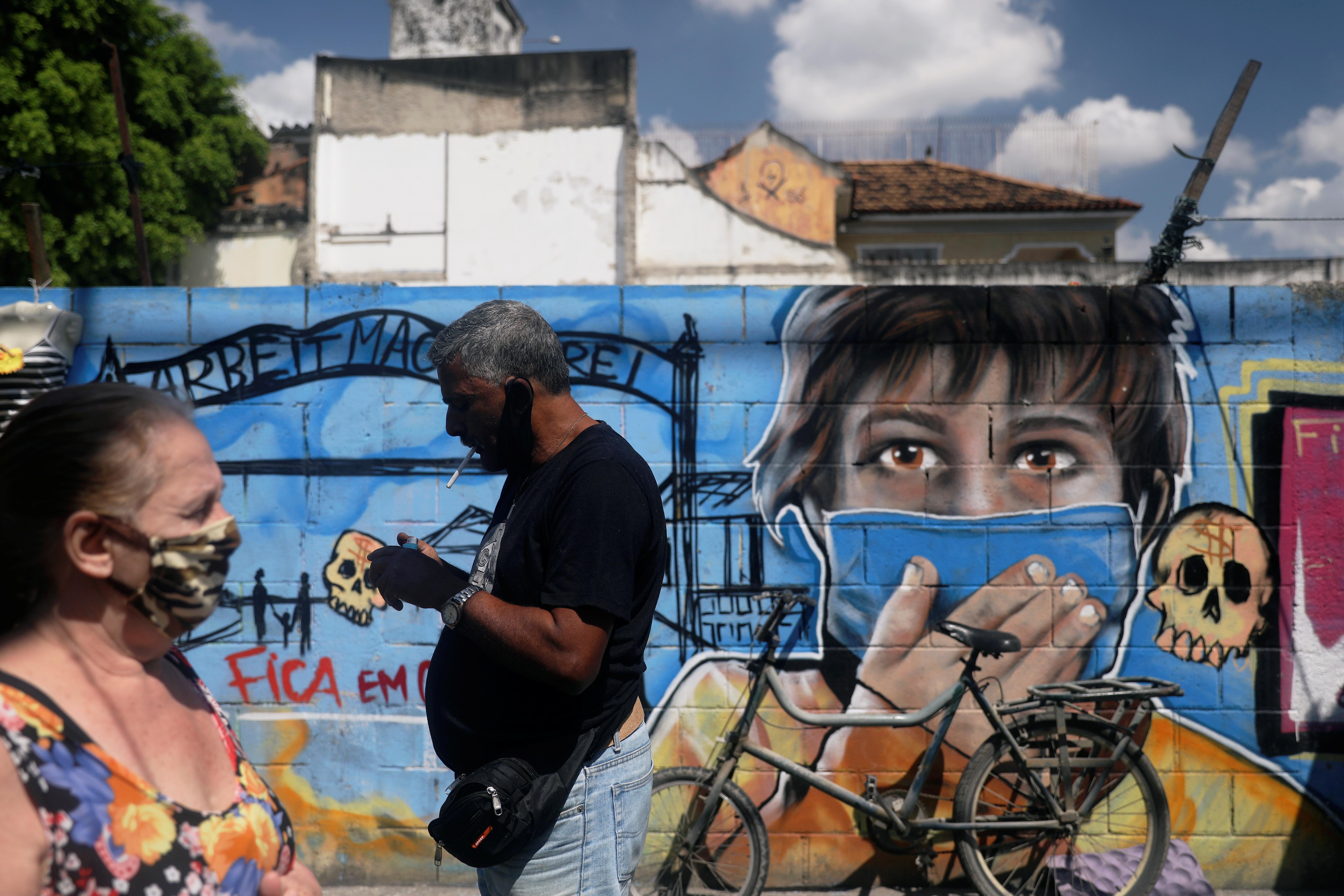 People wearing protective masks walk past a graffiti, following the coronavirus disease (COVID-19) outbreak, in Rio de Janeiro, Brazil September 2, 2020. REUTERS/Pilar Olivares/Files