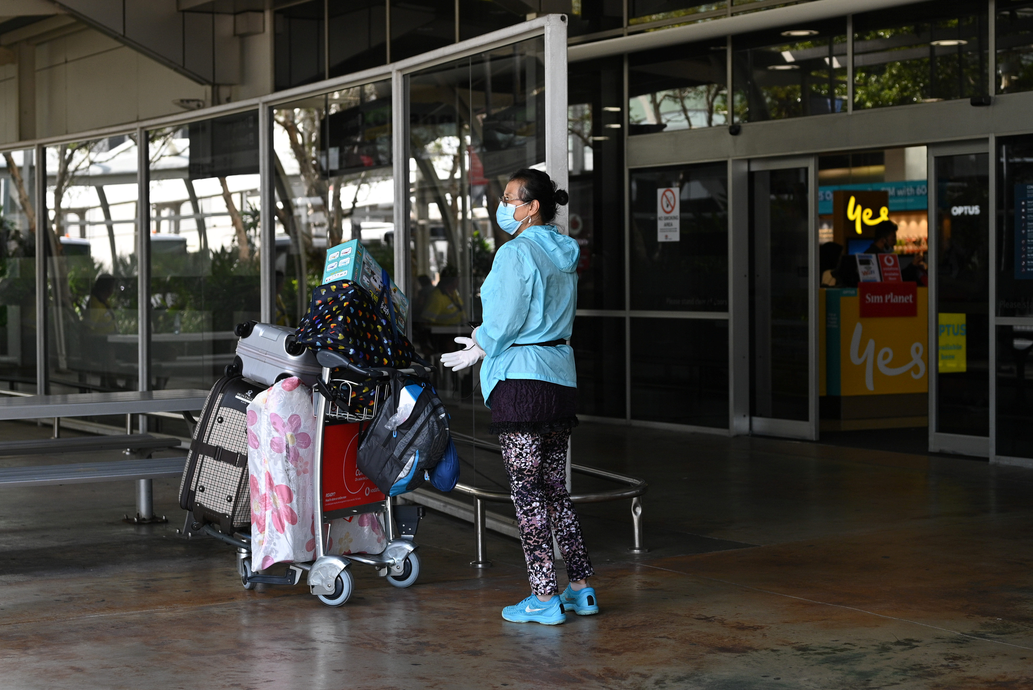A traveler wearing a protective face mask and gloves departs the arrivals section of the international terminal of Kingsford Smith International Airport the morning after Australia implemented an entry ban on non-citizens and non-residents intended to curb the spread of the coronavirus disease (COVID-19) in Sydney, Australia, March 21, 2020.  REUTERS/Loren Elliott