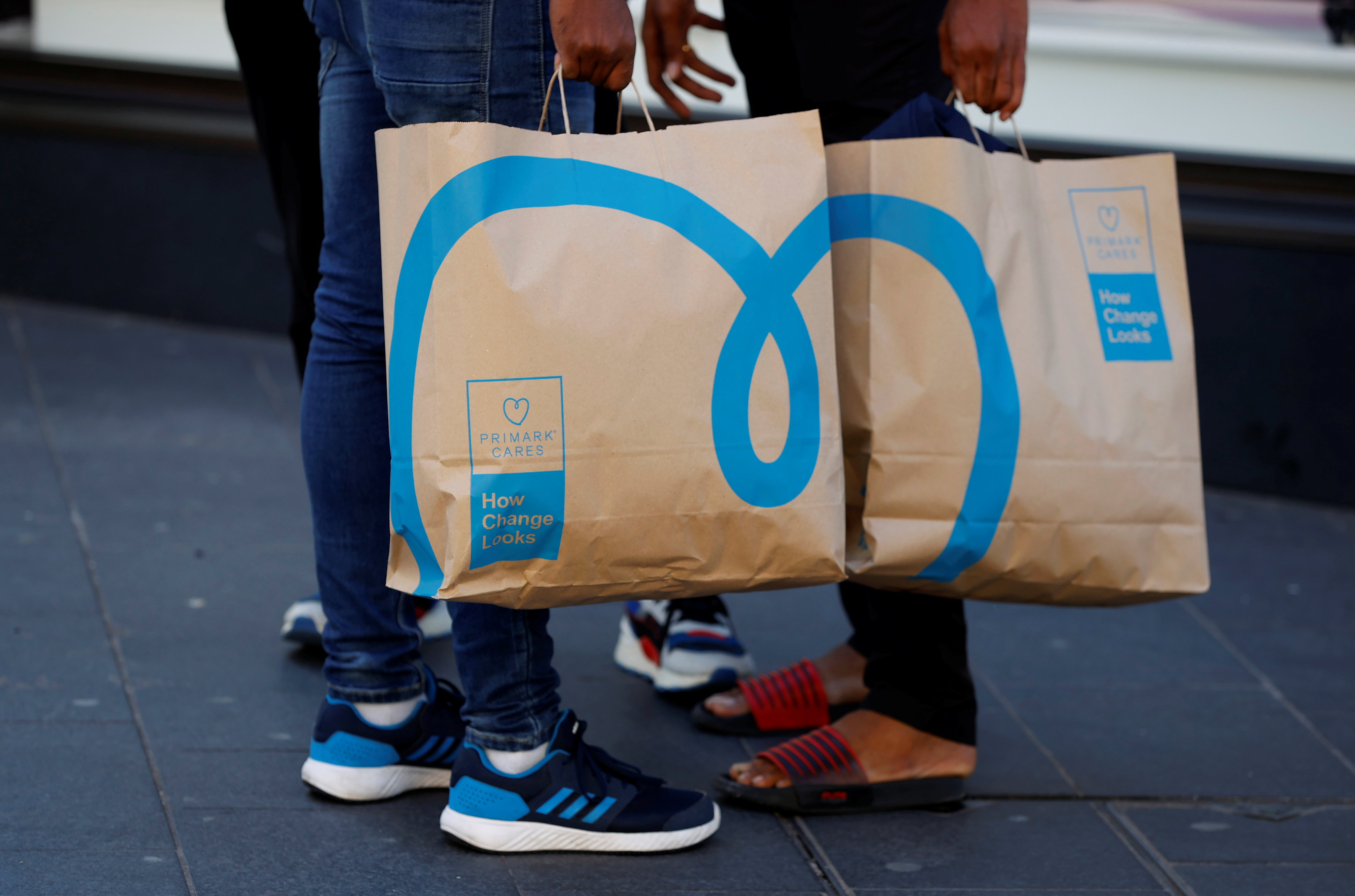 Shoppers holding newly environmentally themed bags stand outside a Primark store in Liverpool, Britain, September 15, 2021. REUTERS/Phil Noble