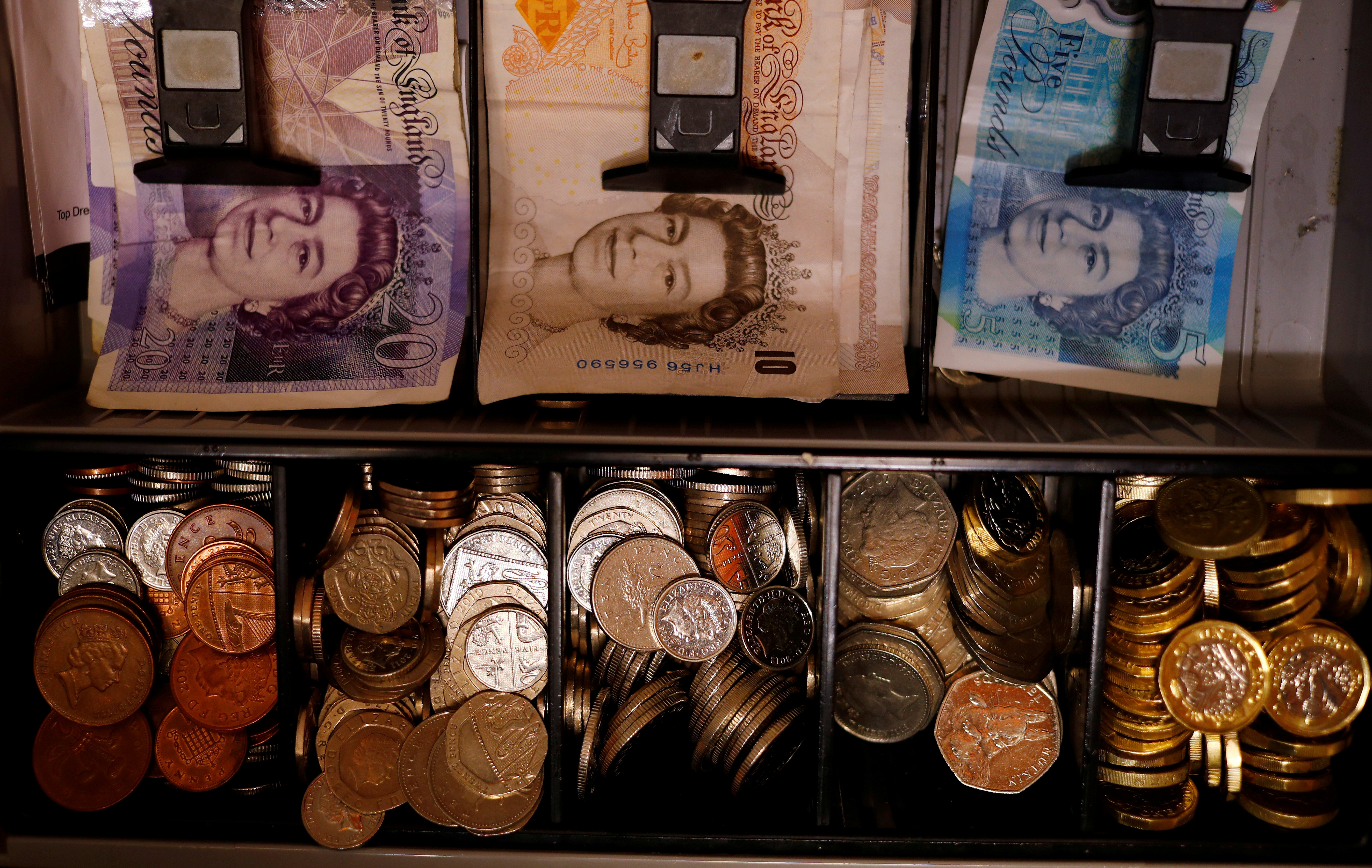 Pound notes and coins are seen inside a cash register in a bar in Manchester, Britain September 6, 2017. REUTERS/Phil Noble//File Photo