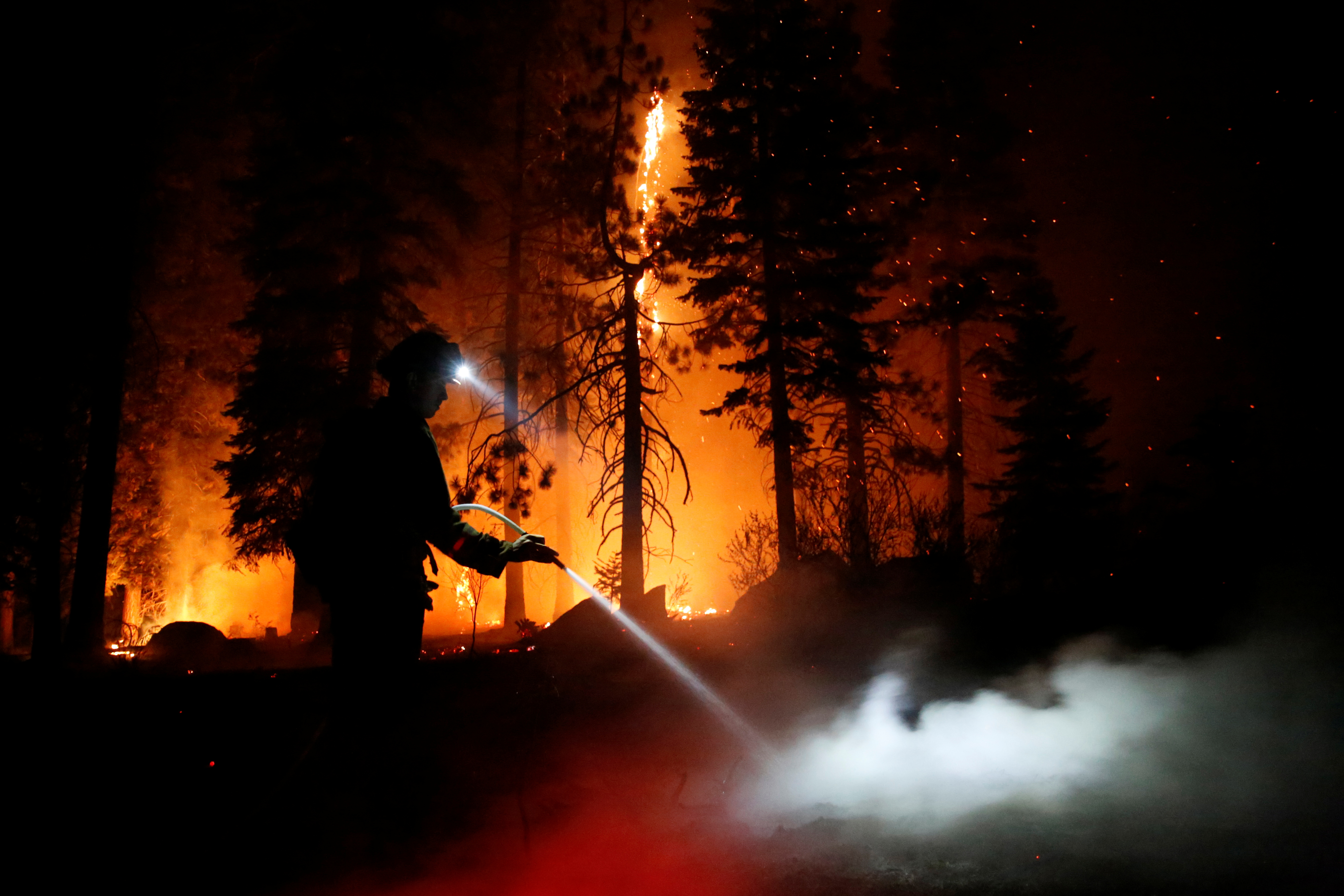 Patrick R., 27, a firefighter with Cal Fire sprays water on hot spots as flames from the Caldor Fire burn through trees in Christmas Valley near South Lake Tahoe, California, U.S., August 31, 2021.    REUTERS/Brittany Hosea-Small