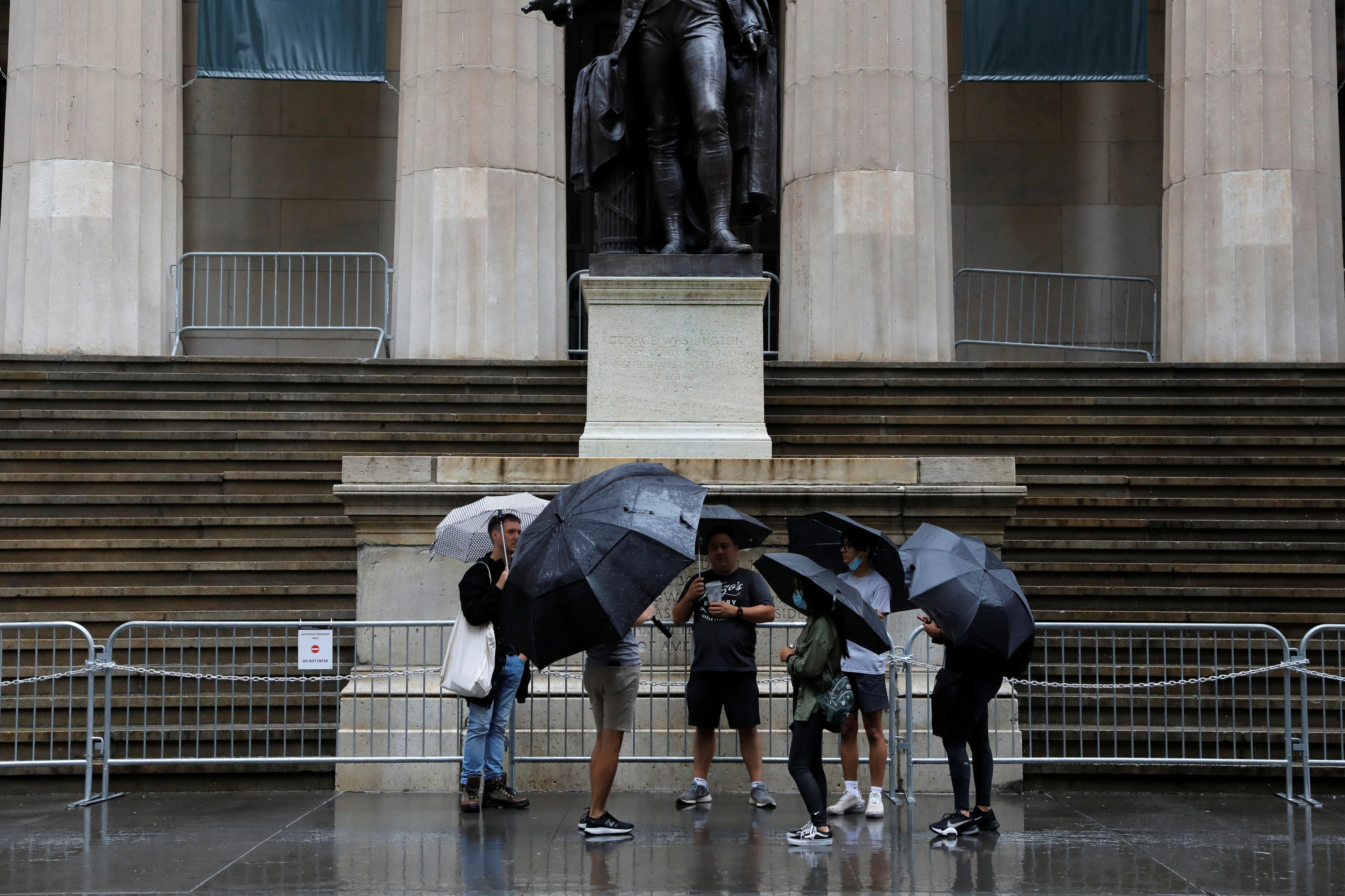 People on an organized Airbnb tour gather near the statue of former U.S. President George Washington outside Federal Hall on Wall Street, as Tropical Storm Henri affected the region in Manhattan, New York City, U.S., August 23, 2021. REUTERS/Andrew Kelly