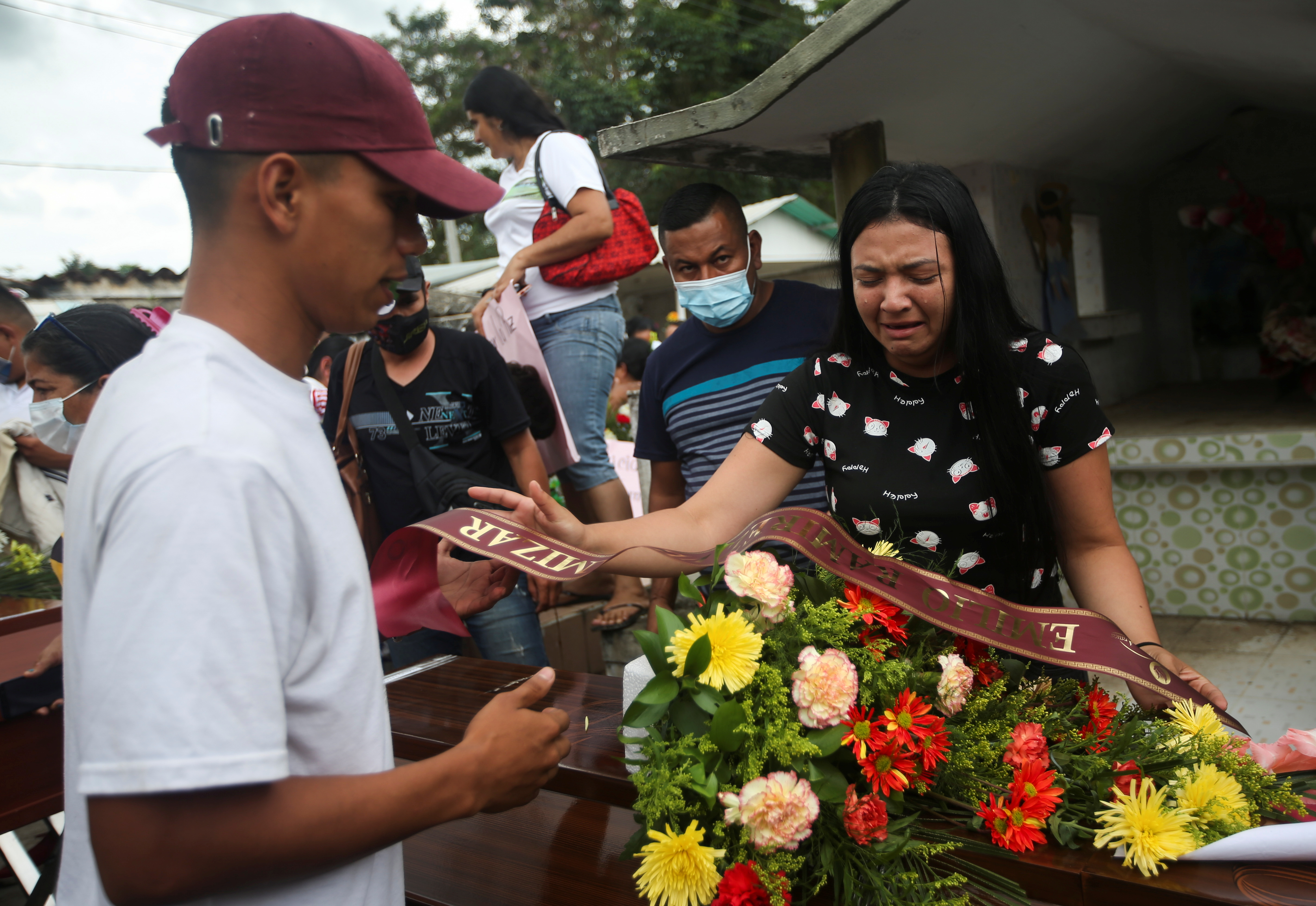 A woman cries next to a coffin with the body of a Venezuelan citizen killed in the middle of the operations of the Bolivarian National Armed Forces, according to his relatives, before being buried in the cemetery of Arauquita, Colombia March 29, 2021. REUTERS/Luisa Gonzalez