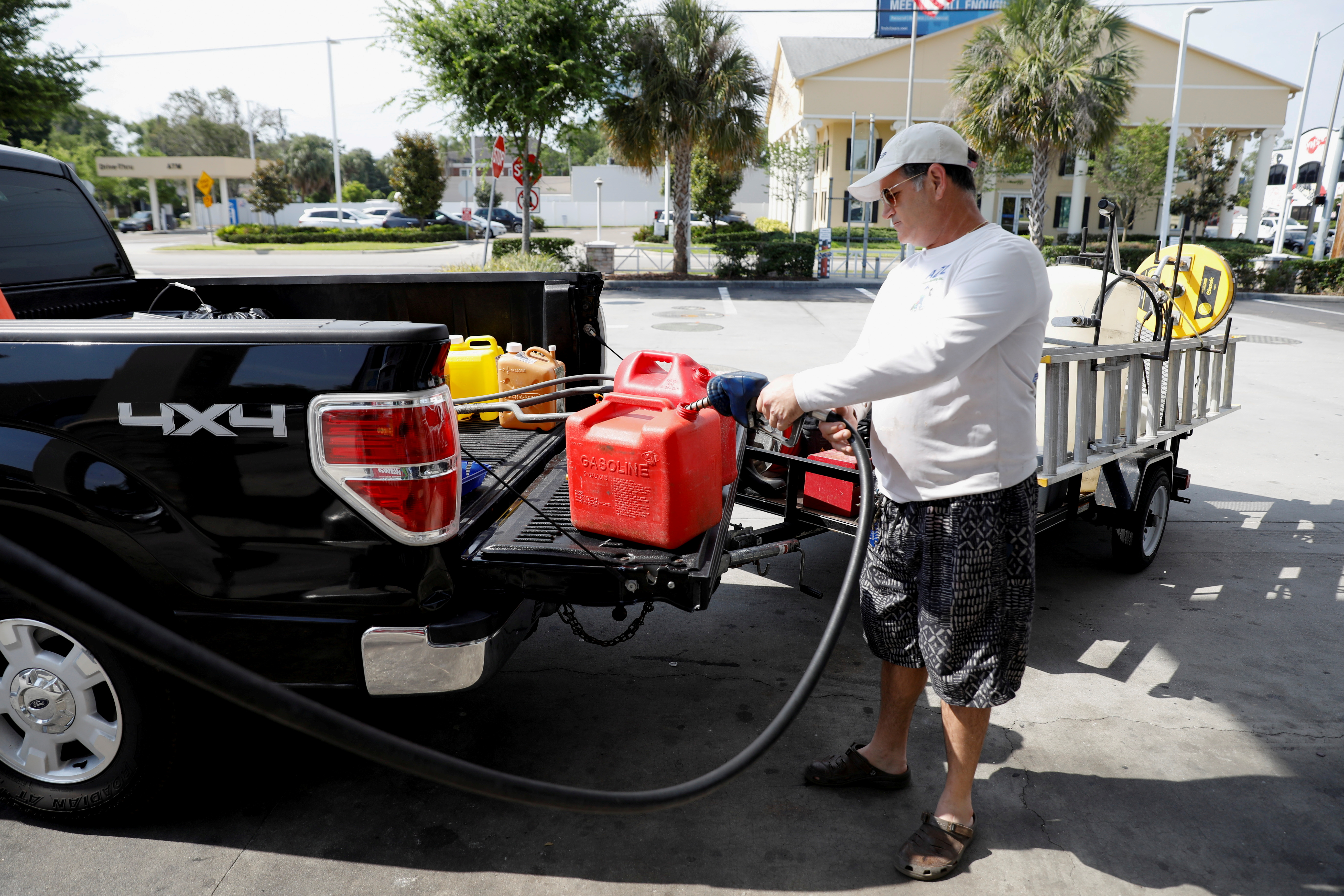 Dax Valenti fills up gas tanks at a gas station after a cyberattack crippled the biggest fuel pipeline in the country, run by Colonial Pipeline, in Tampa, Florida, U.S., May 12, 2021. REUTERS/Octavio Jones/File Photo