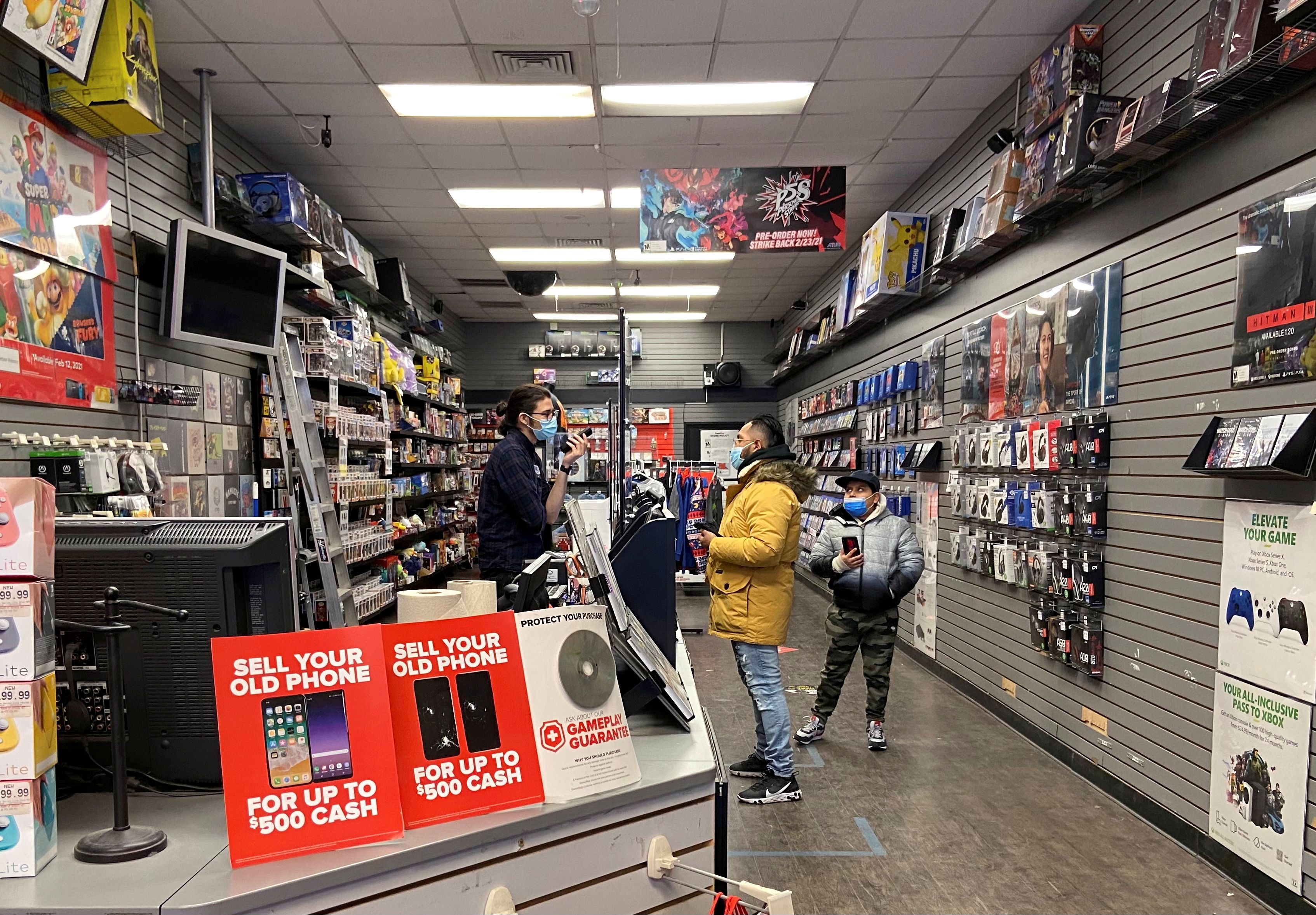 An employee talks with a customer at a GameStop shop in New York City, New York, U.S. January 30, 2021. Picture taken January 30, 2021. REUTERS/Nick Zieminski/File Photo