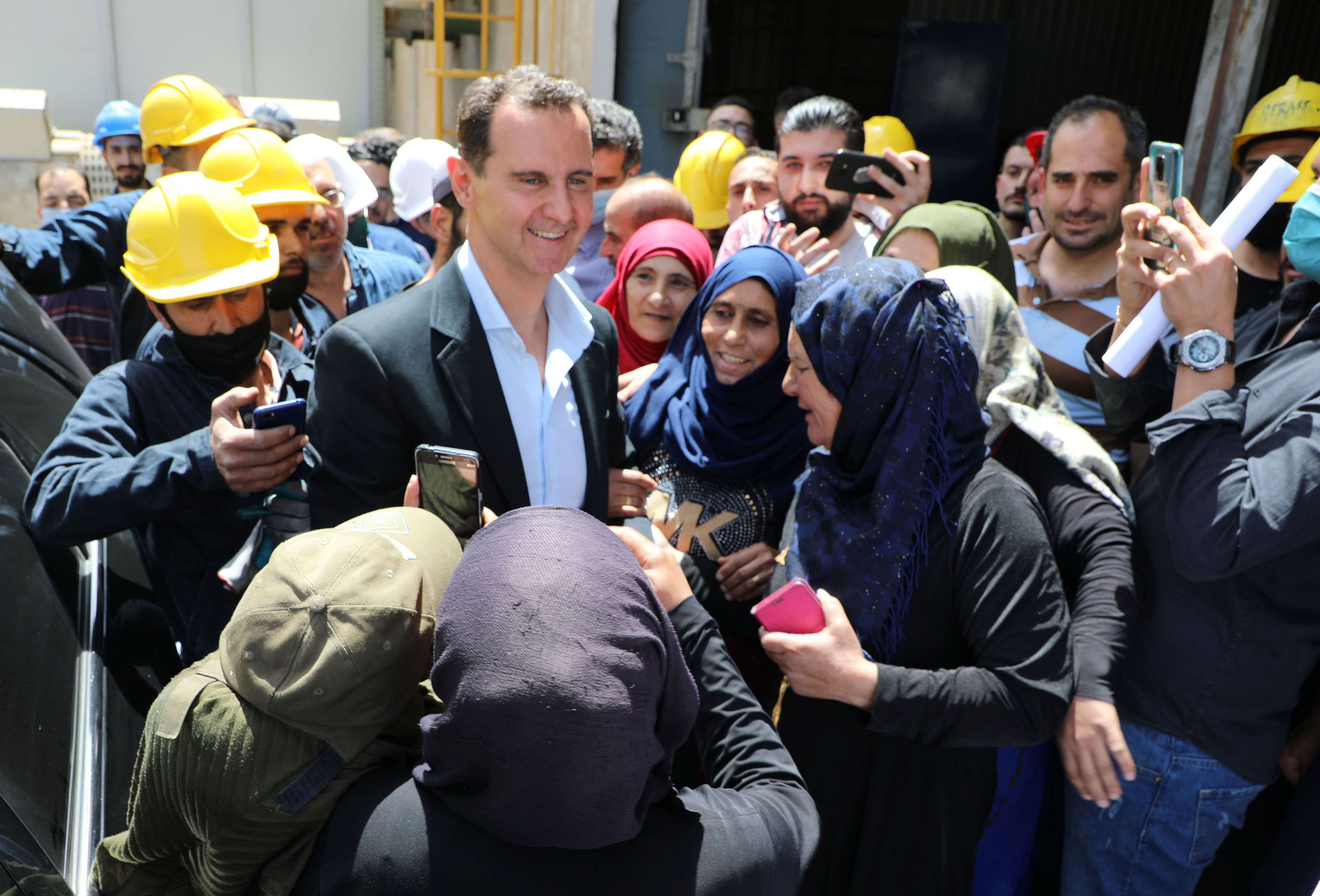 Syrian President Bashar al-Assad meets with people during his visit to some factories and facilities in the industrial city of Hassia in Homs, Syria in this handout picture released on May 3, 2021. SANA/Handout via REUTERS