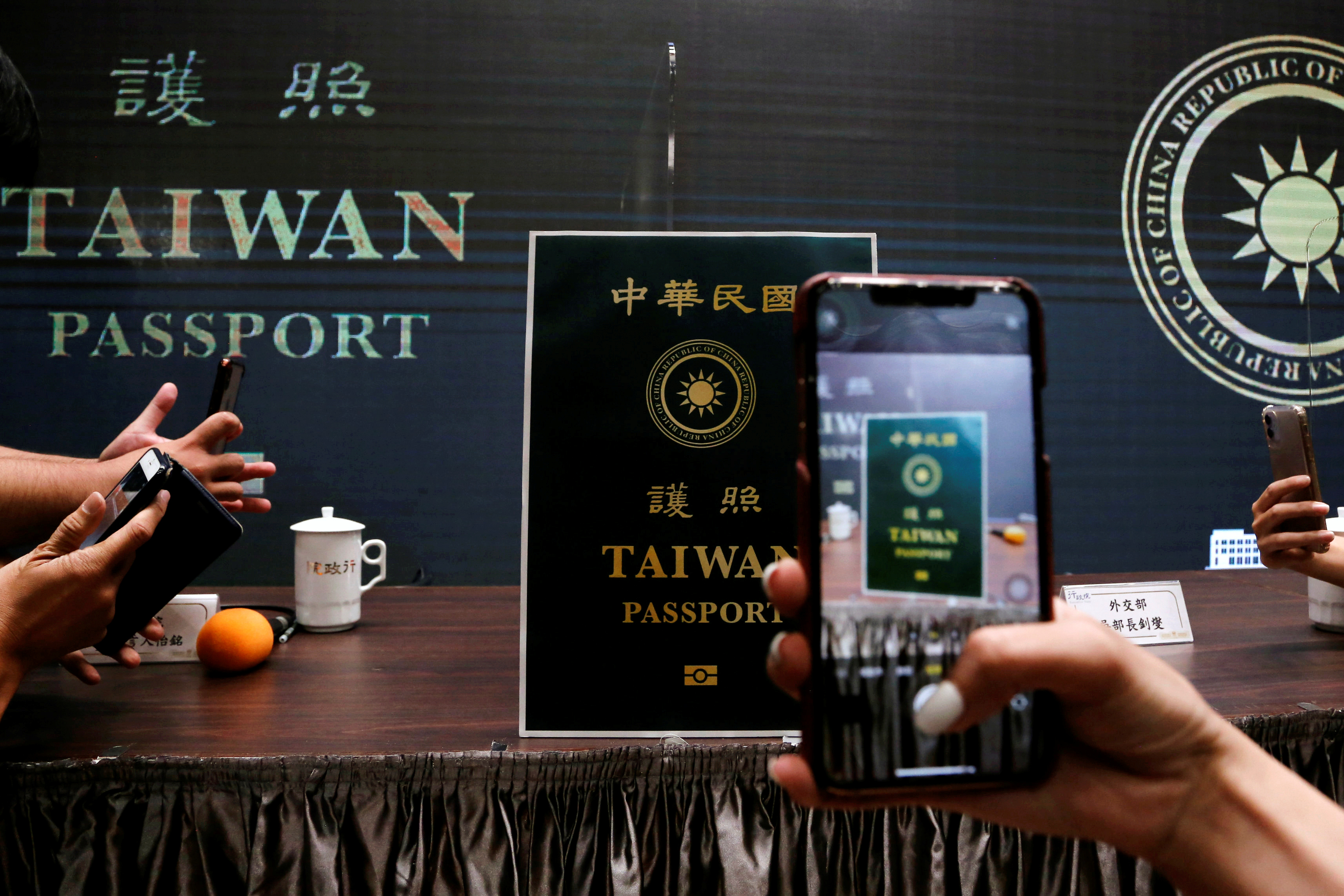 Members of the media take photos of a paper cut out of the new Taiwan passport displayed in Taipei, Taiwan, September 2, 2020. REUTERS/Ann Wang
