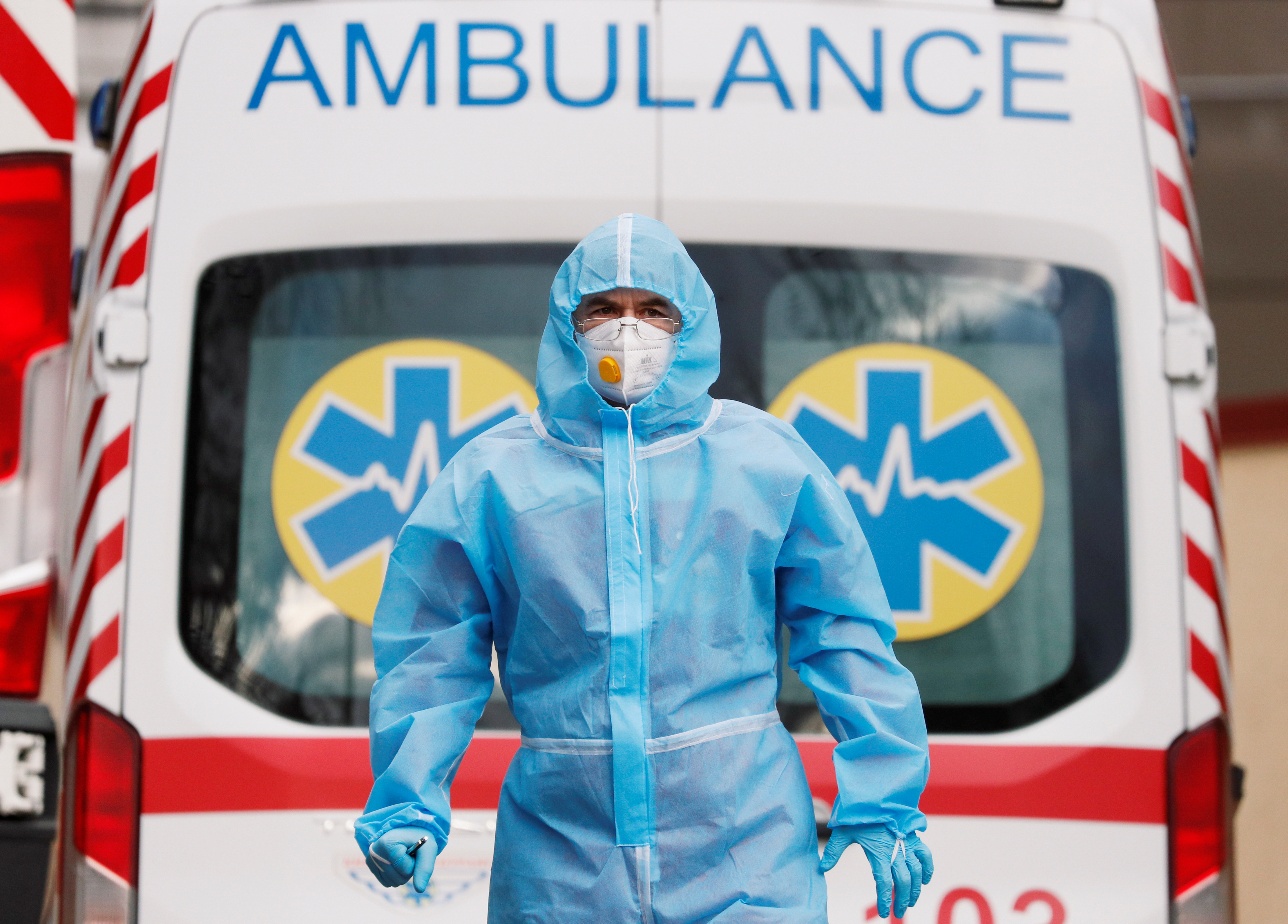 A medical worker wearing protective gear stands next to an ambulance outside a hospital for patients infected with the coronavirus disease (COVID-19) in Kyiv, Ukraine November 24, 2020.  REUTERS/Gleb Garanich
