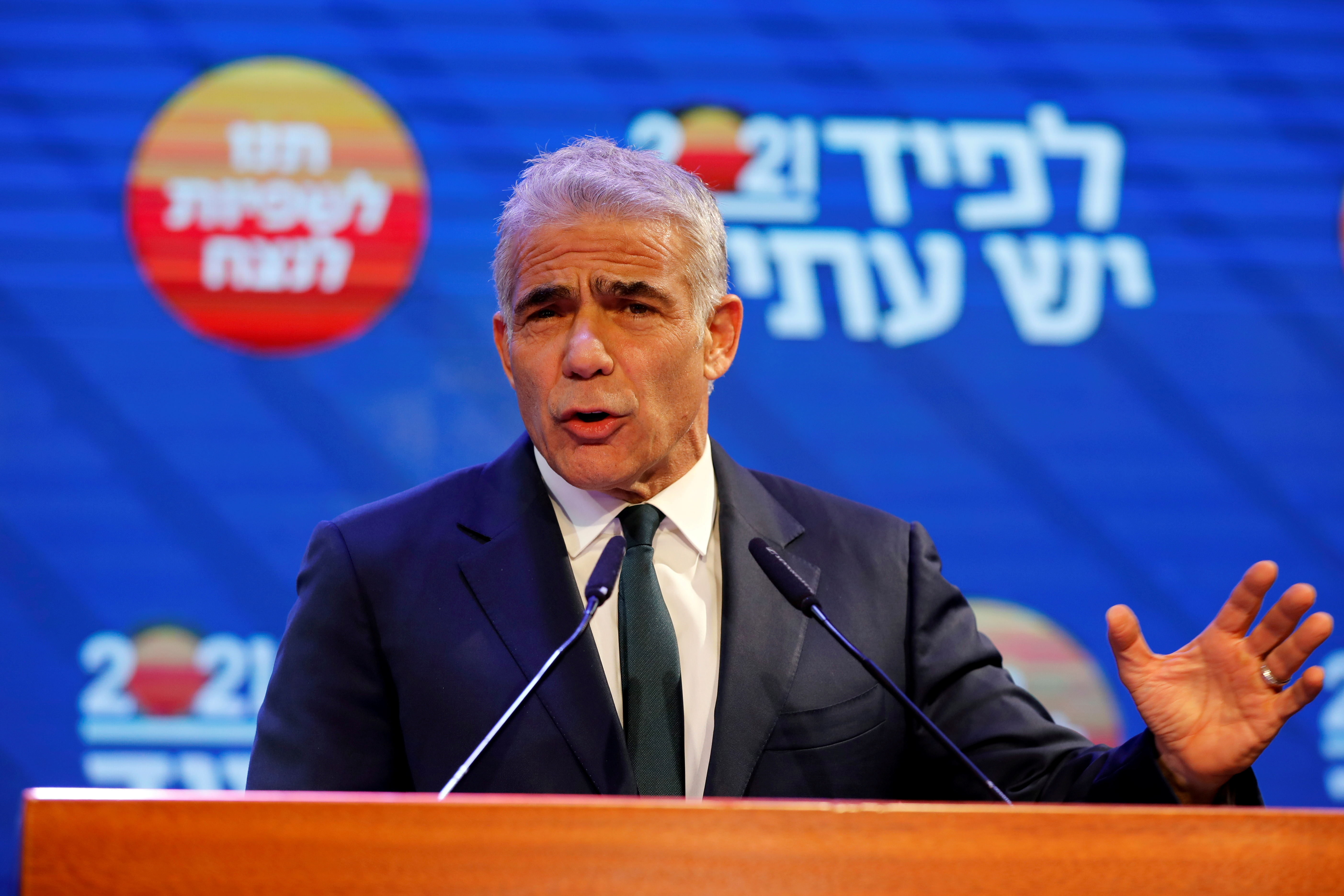 Yesh Atid party leader Yair Lapid gestures as he delivers a speech following the announcement of exit polls in Israel's general election at his party headquarters in Tel Aviv, Israel March 24, 2021. REUTERS/Amir Cohen