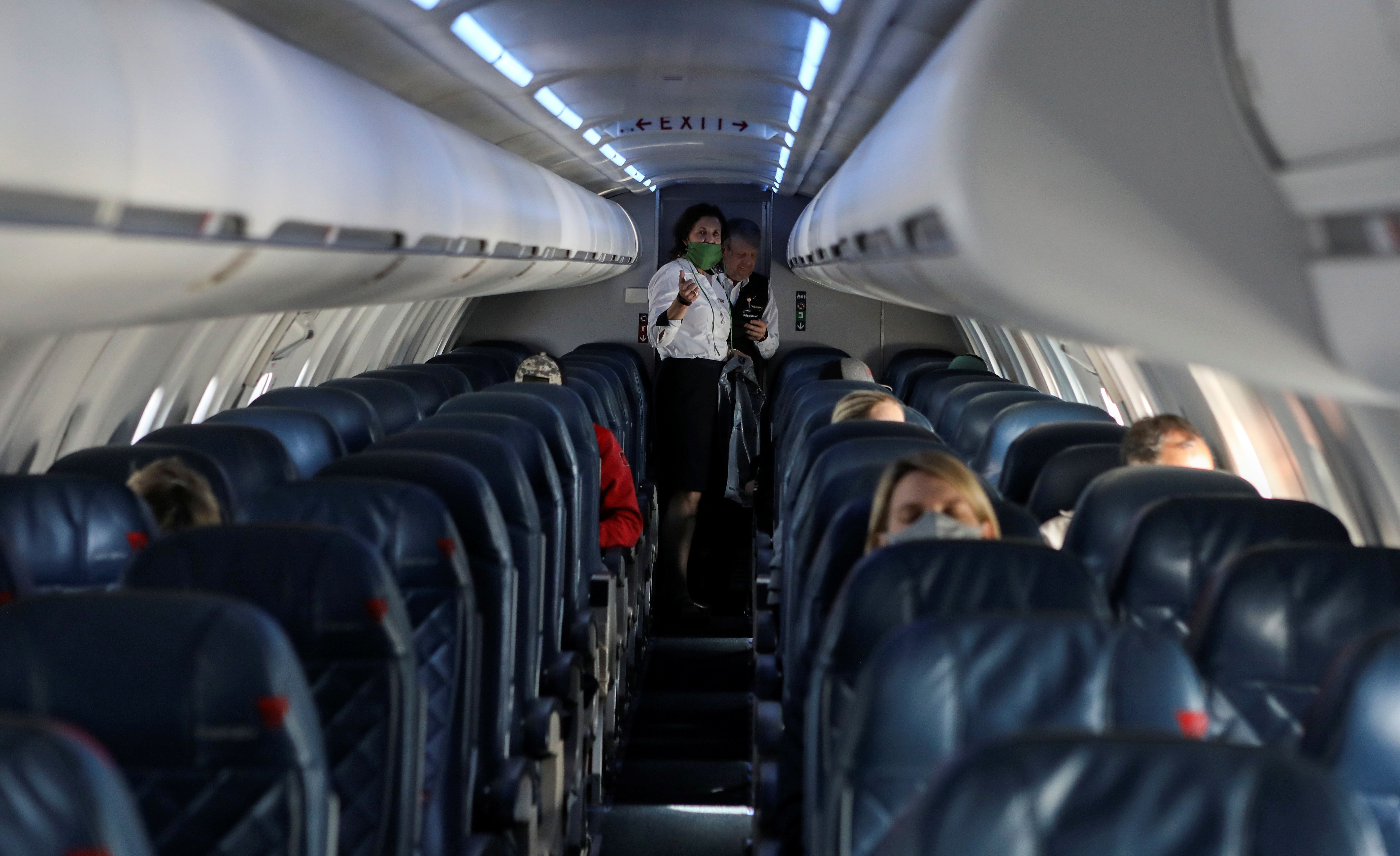 Flight attendants talk in a nearly empty cabin on a Delta Airlines flight operated by SkyWest Airlines as travel has cutback, amid concerns of the coronavirus disease (COVID-19), during a flight departing from Salt Lake City, Utah, U.S. April 11, 2020. REUTERS/Jim Urquhart