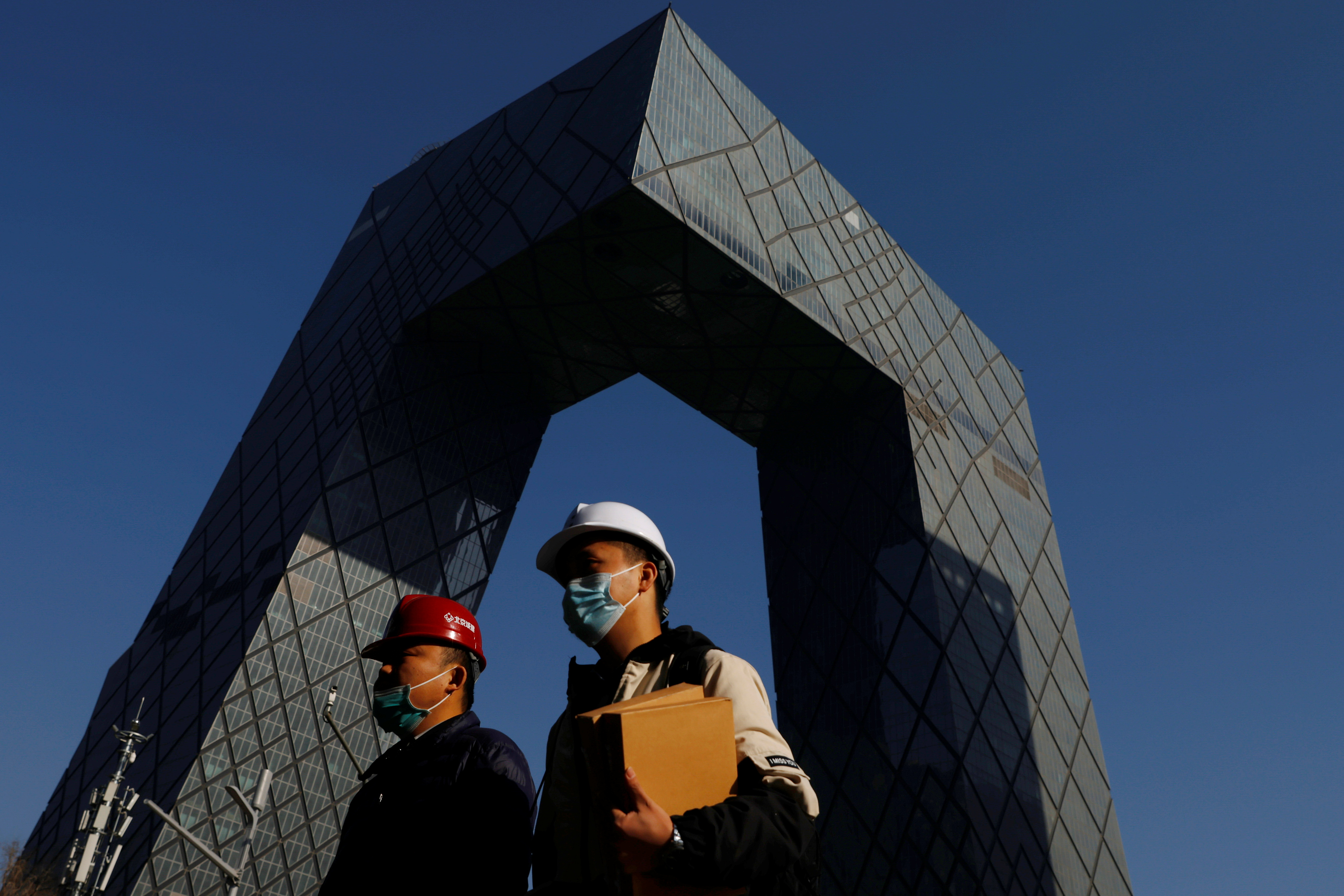 People wearing face masks following the coronavirus disease (COVID-19) outbreak walk past the CCTV headquarters, the home of Chinese state media outlet CCTV and its English-language sister channel CGTN, in Beijing, China February 5, 2021. REUTERS/Carlos Garcia Rawlins/Files