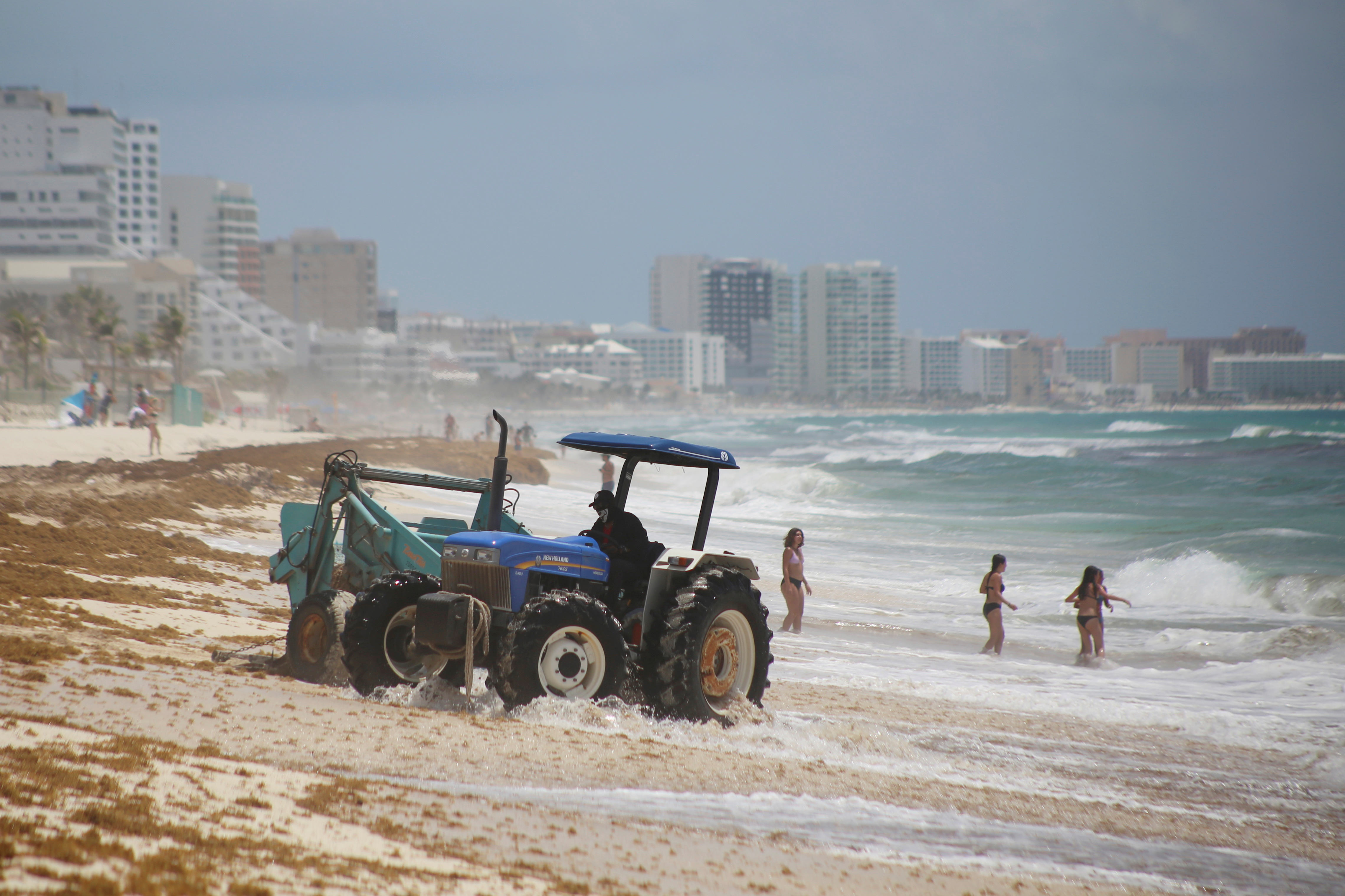 A tractor pulls a trailer with sargassum at Marlin Beach as tourists enjoy the beach in Cancun, Mexico July 23, 2021. REUTERS/Paola Chiomante