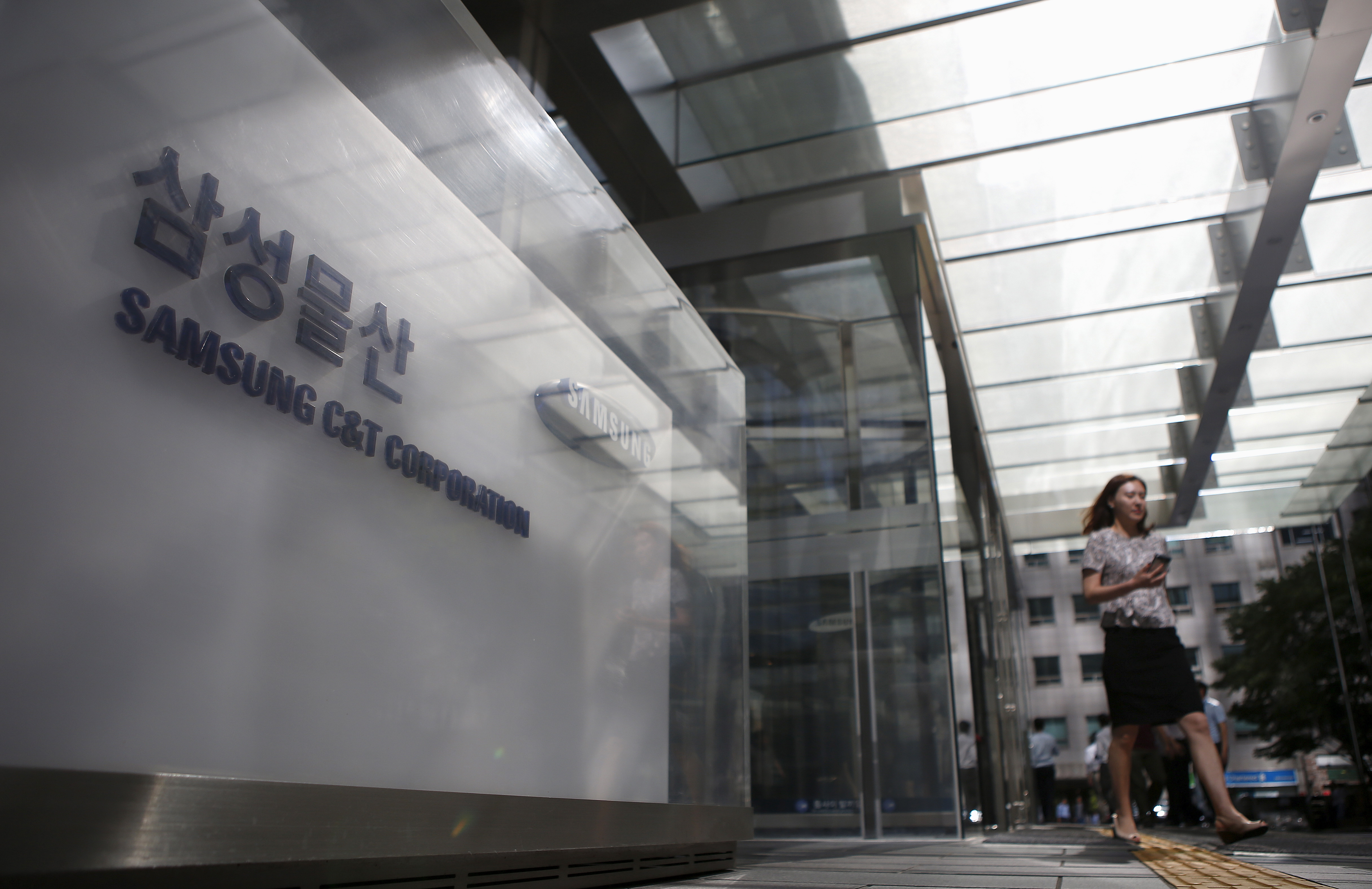 An employee walks past a logo of Samsung C&T Corp at the company's headquarters in Seoul, South Korea, July 16, 2015. REUTERS/Kim Hong-Ji