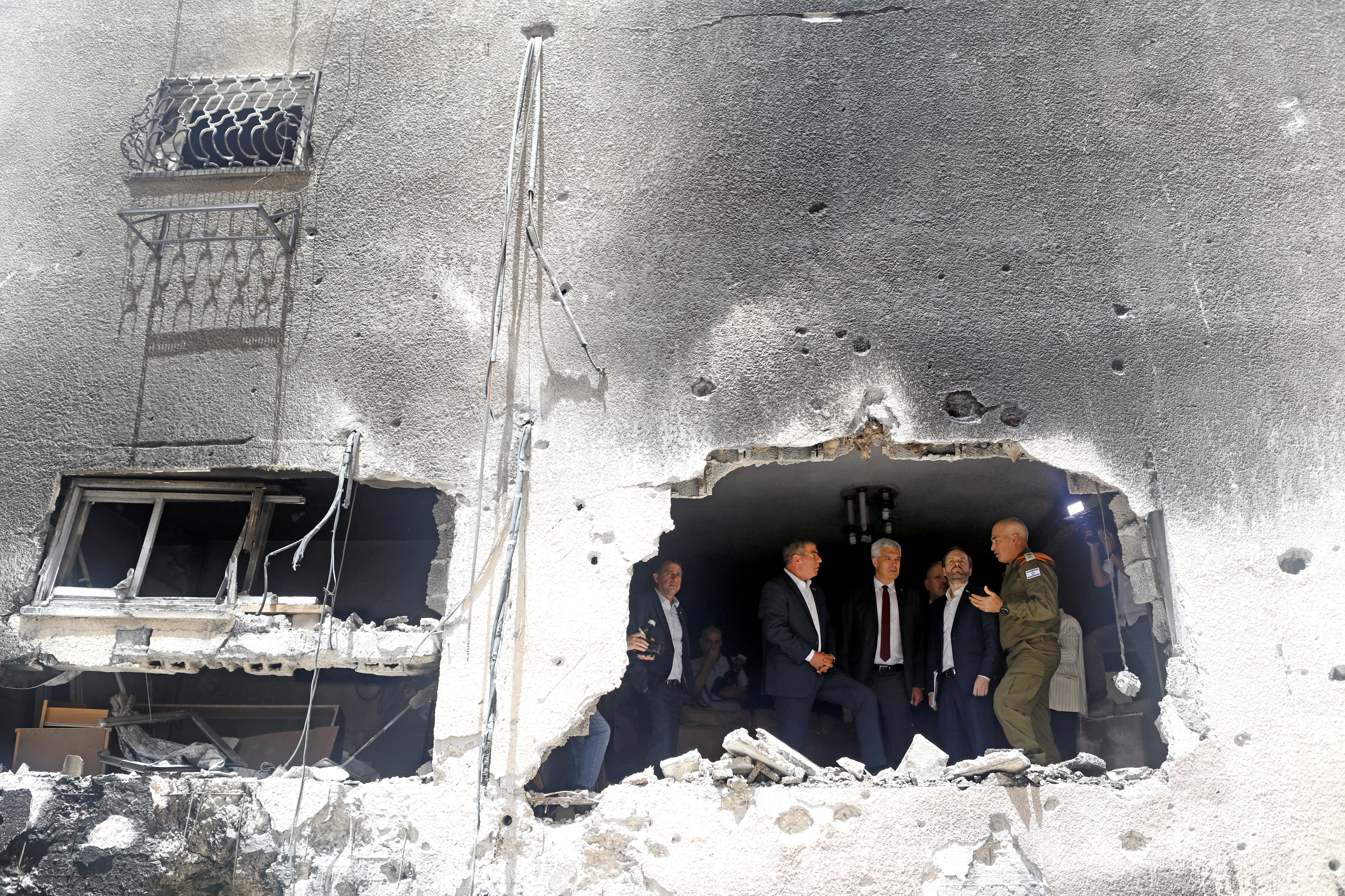 Israeli Foreign Minister Gabi Ashkenazi speaks to his Czech counterpart Jakub Kulhanek and Slovak counterpart Ivan Korcok as they visit the site of a building damaged by a rocket launched from the Gaza Strip last week, in Petah Tikva, Israel May 20, 2021. REUTERS/Nir Elias