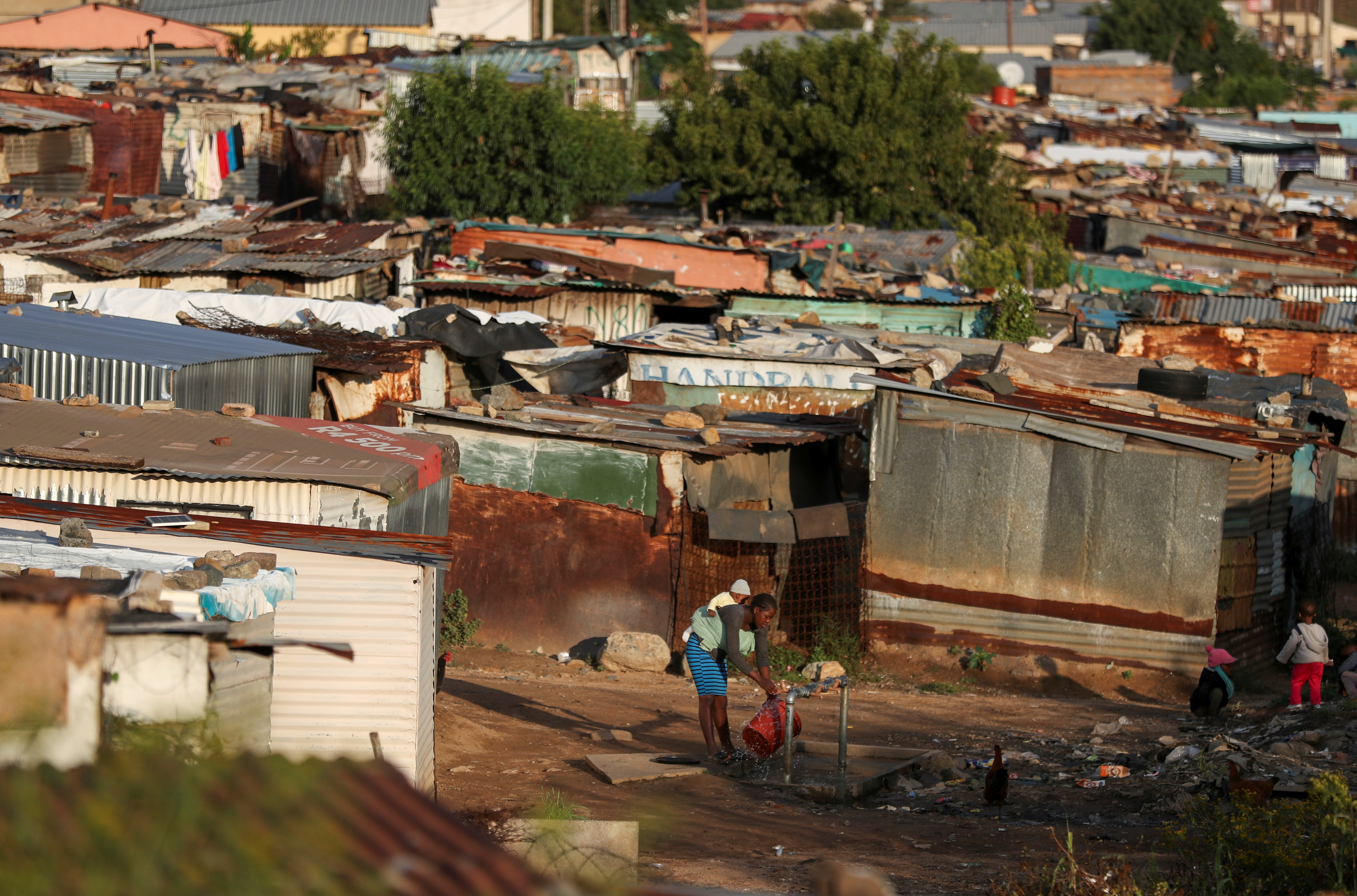 A woman with a baby on her back collects water at an informal settlement as the coronavirus disease (COVID-19) lockdown regulations ease in Soweto, South Africa, April 7, 2021. REUTERS/Siphiwe Sibeko
