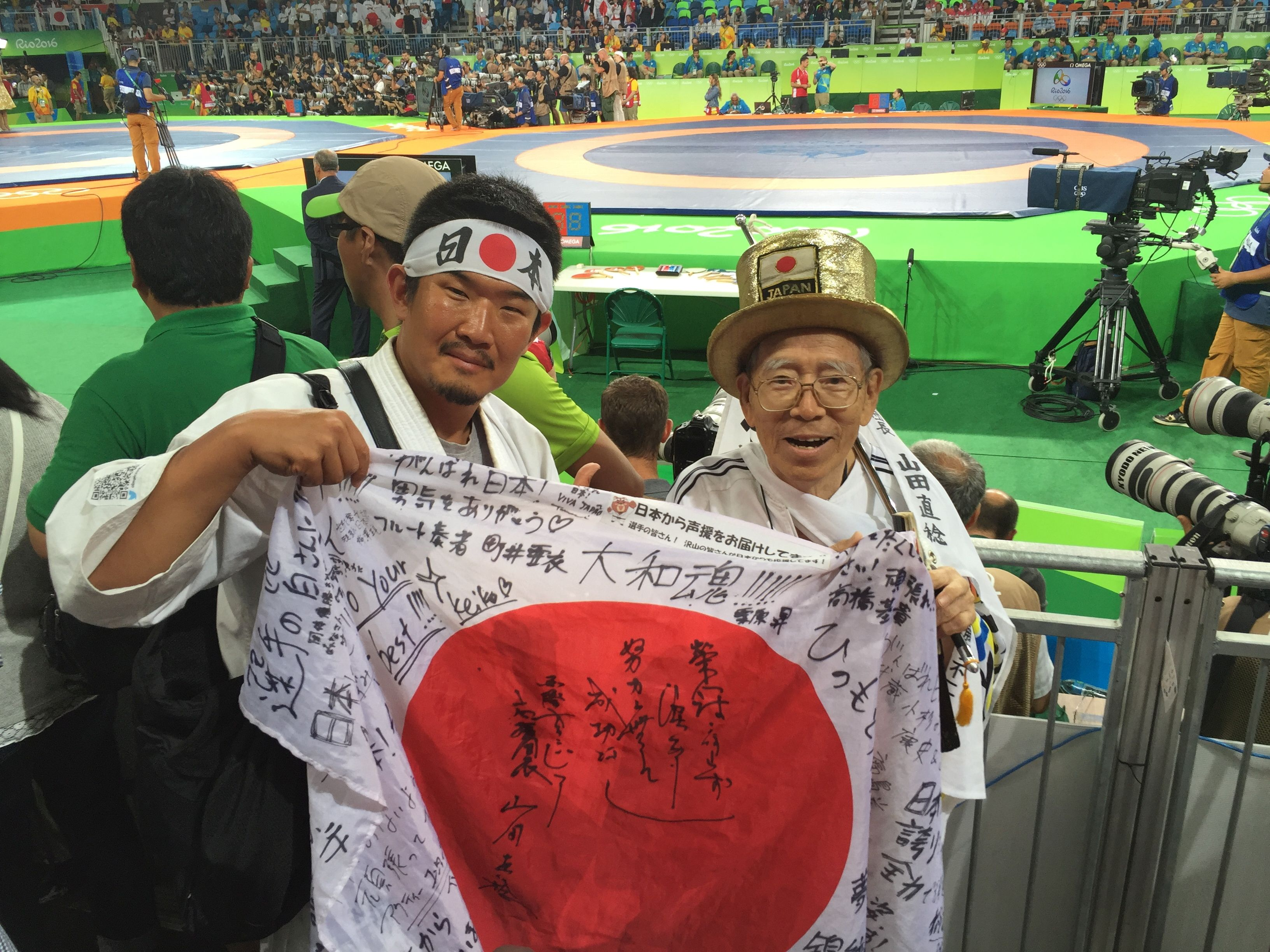 Kazunori Takishima poses with a Japanese fan at a wrestling venue of the Rio 2016 Olympic Games in Rio de Janeiro, Brazil, August 18, 2016.   Kazunori Takishima/Handout via REUTERS