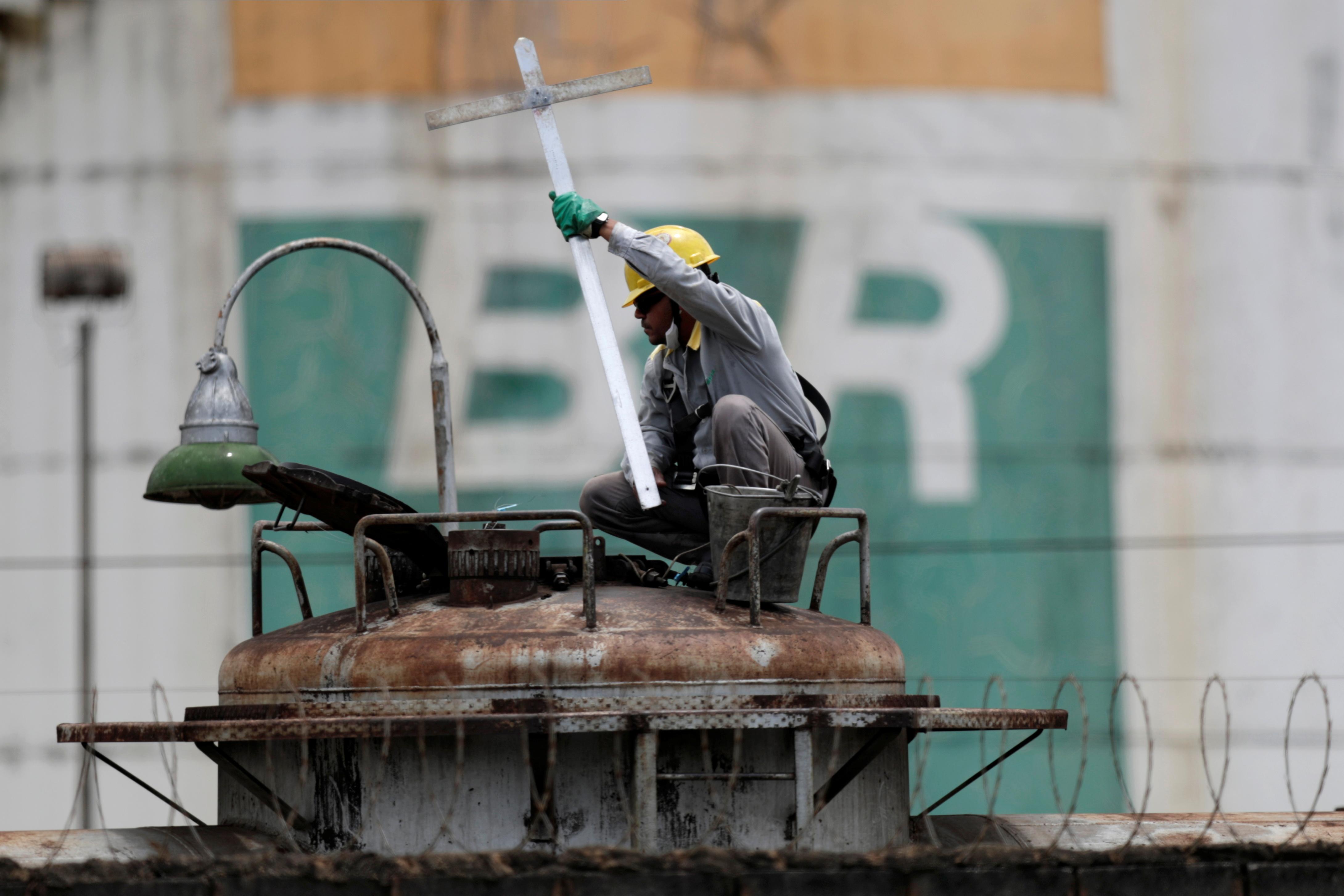 A worker checks the fuel volumes on a train wagon near a tank of Brazil's state-run Petrobras oil company in Brasilia, Brazil, February 19, 2021. REUTERS/Ueslei Marcelino - RC2VVL9V46QF