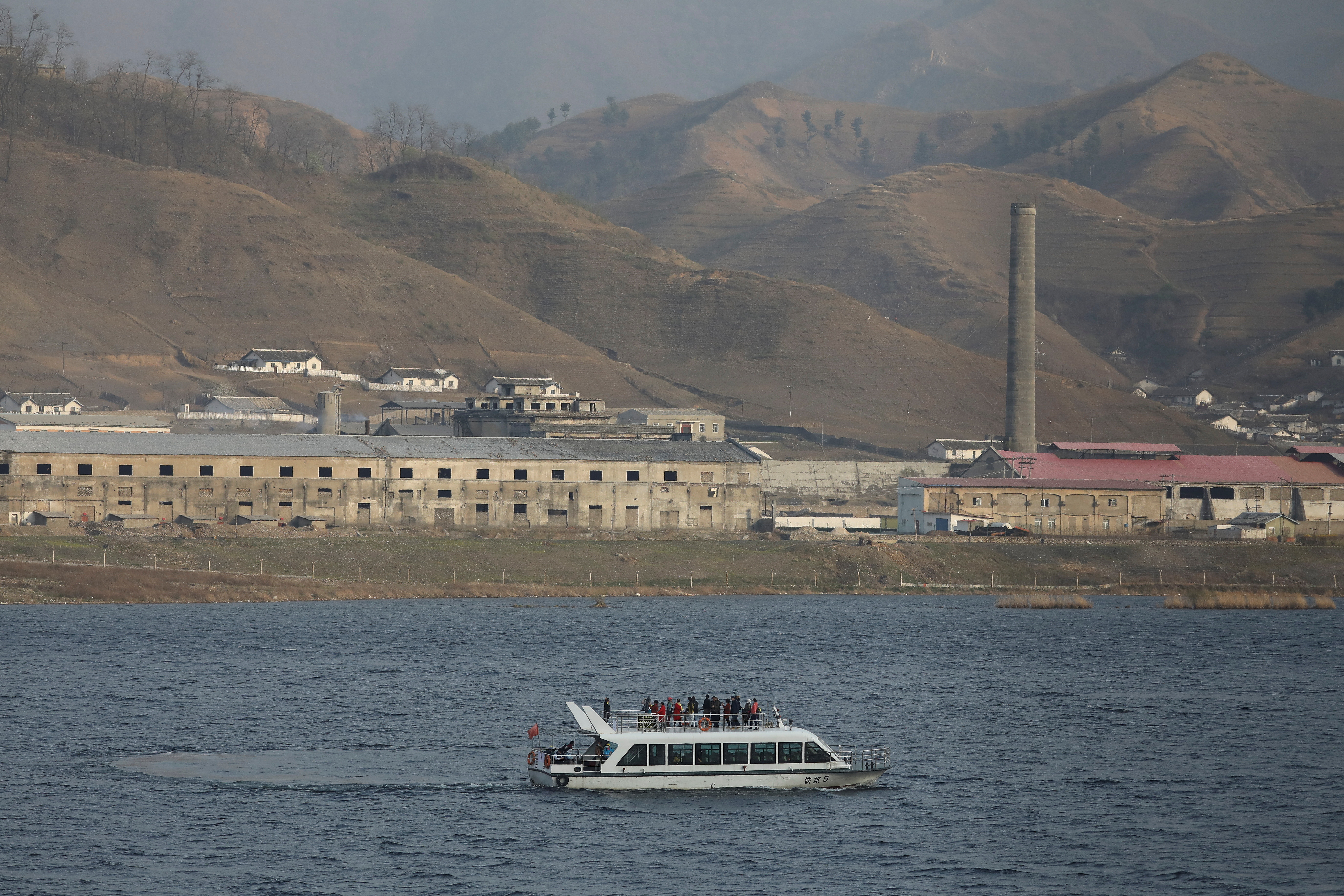 A Chinese cruise boat passes buildings in North Korea's Sinuiju on the Yalu River separating North Korea and China, in Dandong, Liaoning province, China April 20, 2021.   REUTERS/Tingshu Wang