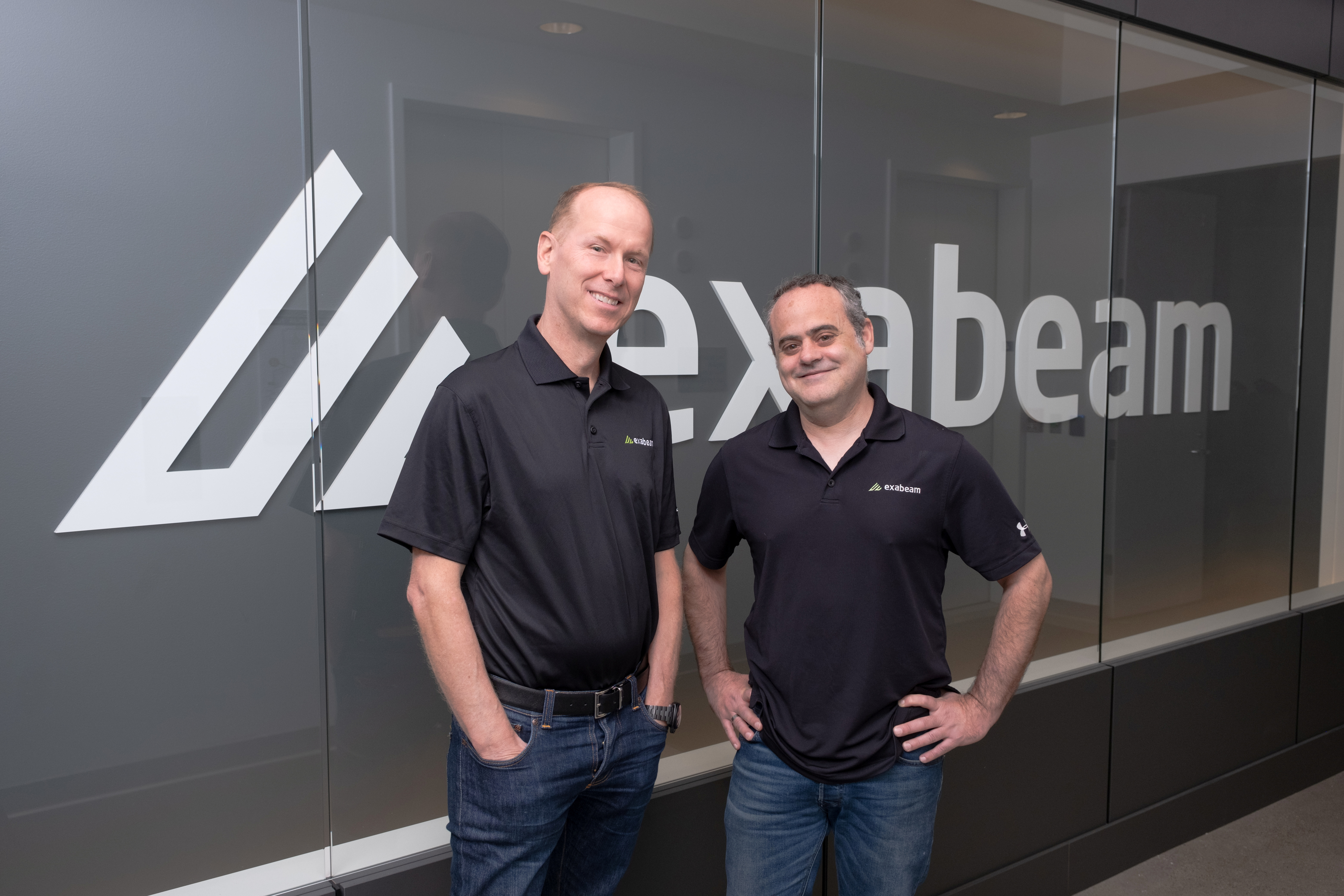 Exabeam CEO Michael DeCesare (L) and chairman and co-founder Nir Polak (R) pose in front of the Exabeam logo in Foster City, California, U.S. in this undated May 2021 handout photograph. Courtesy BIGSHOT PHOTOGRAPHY/Handout via REUTERS