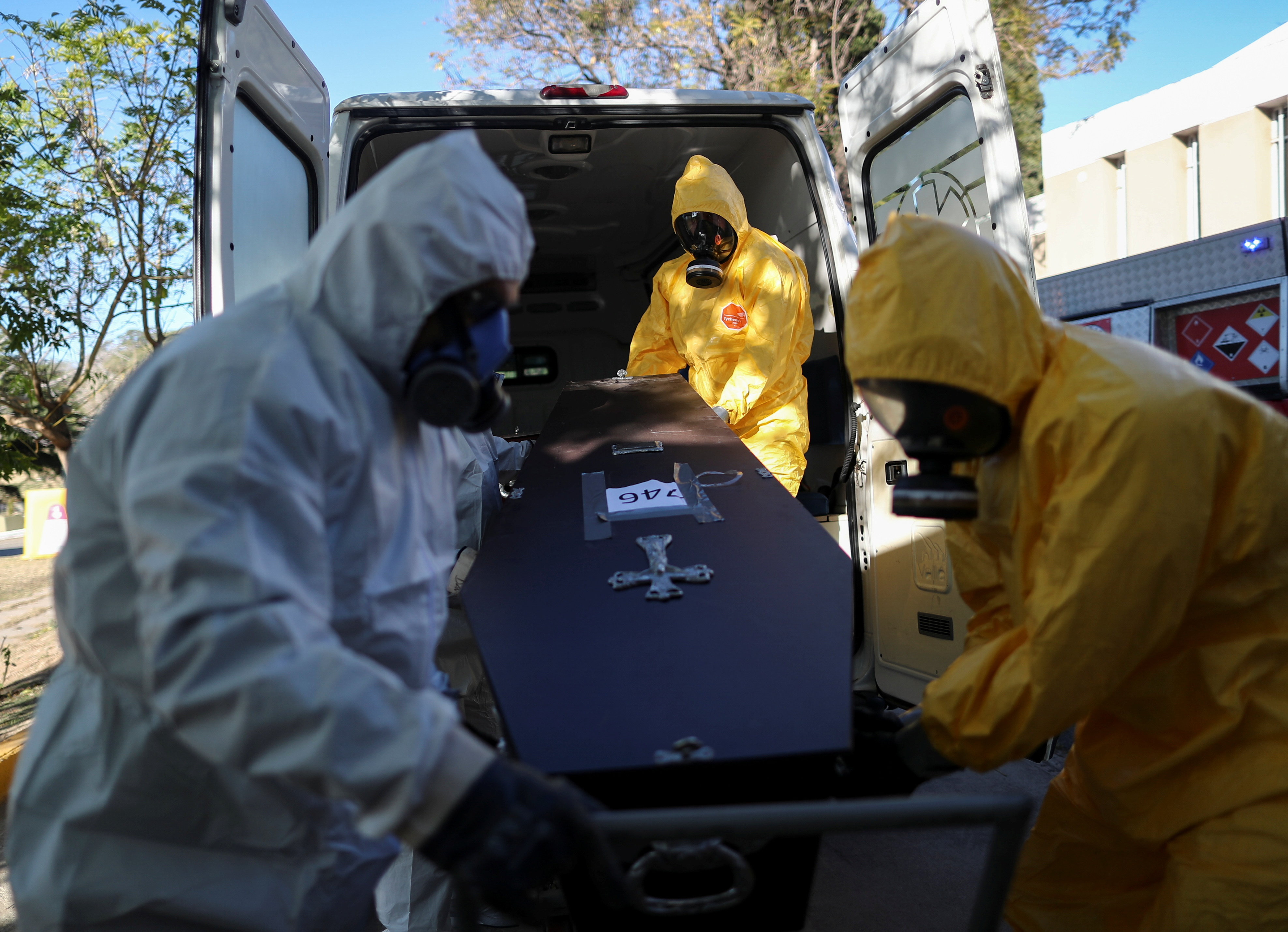 Members of the Department of High Risk Units (DUAR) unload a coffin of a person who died from the coronavirus disease (COVID-19) from an ambulance at the San Vicente cemetery, in Cordoba, Argentina, July 10, 2021. REUTERS/Agustin Marcarian