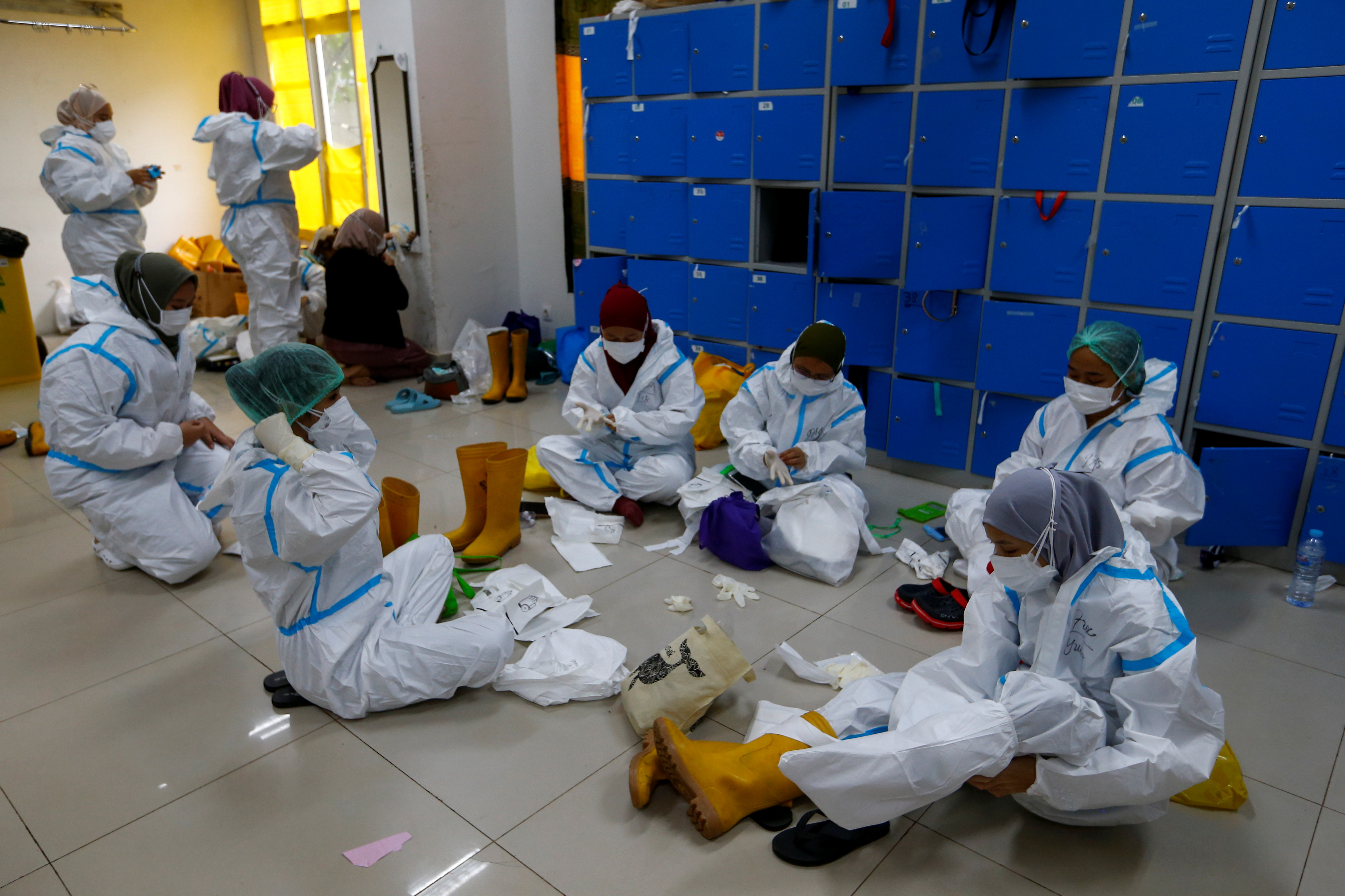 Healthcare workers put on personal protective equipment (PPE) as they prepare to treat patients at the emergency hospital for the coronavirus disease (COVID-19) in Jakarta, Indonesia, June 17, 2021. REUTERS/Ajeng Dinar Ulfiana